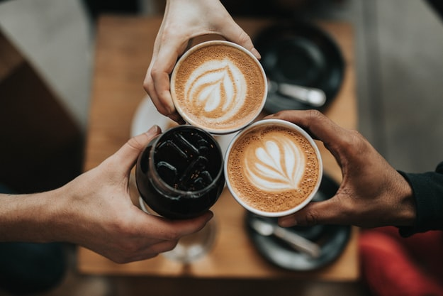 Three coffee lovers cheer their iced and hot cups of coffee