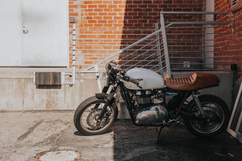 white and brown cruiser motorcycle beside gray steel railings