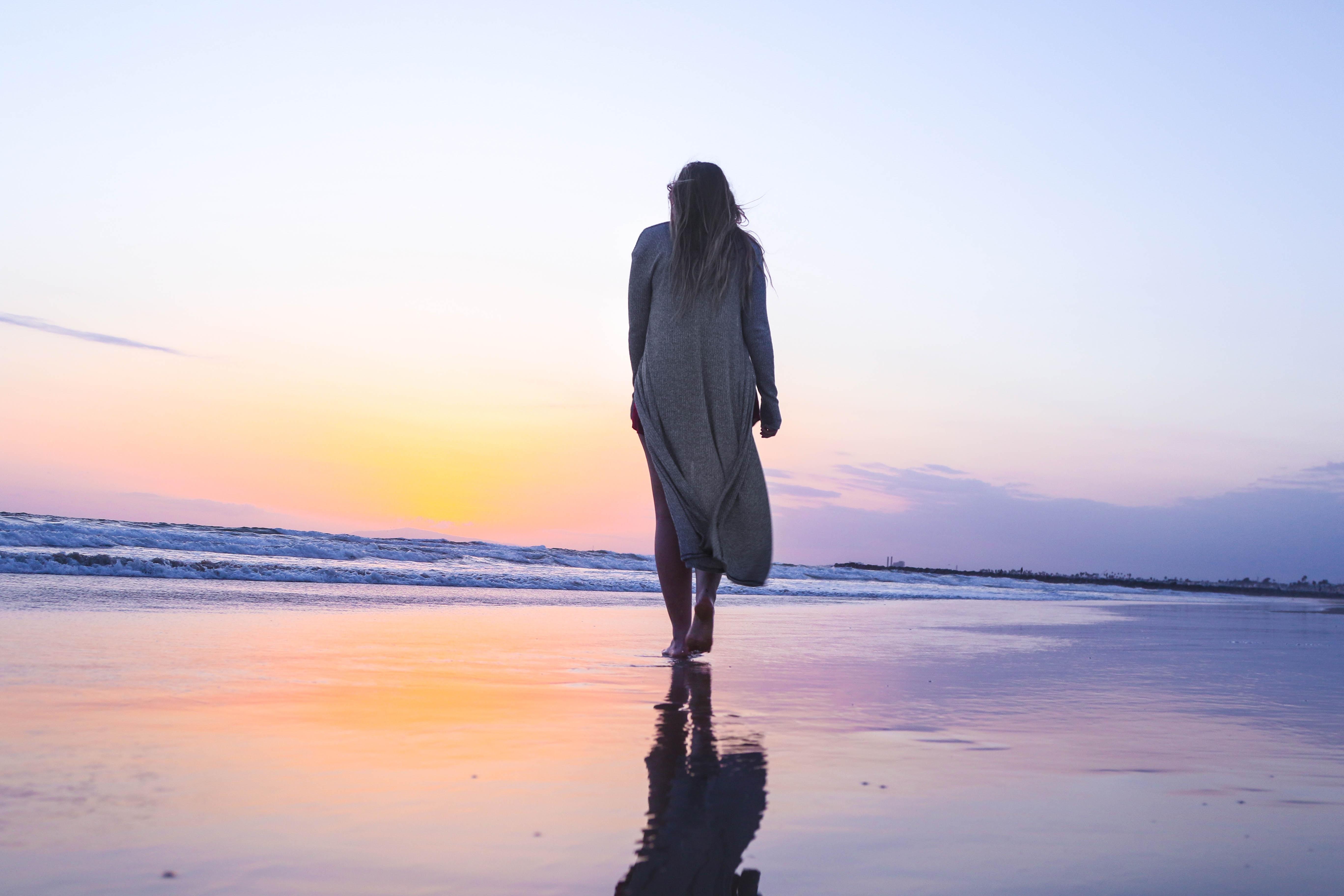 Woman walking on a wet sand beach towards the sunset at Newport Beach