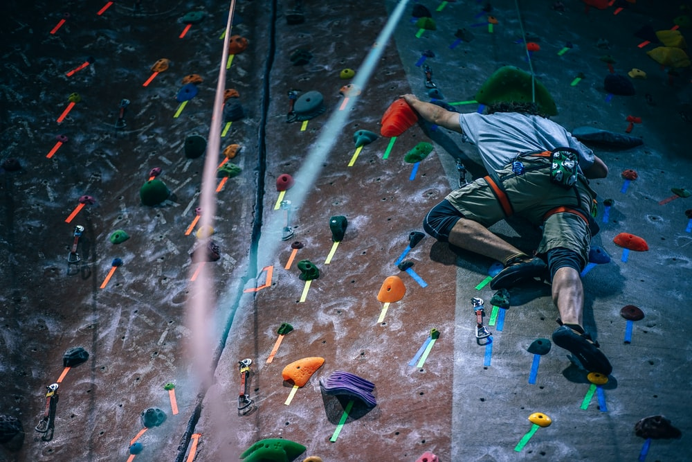 man climbing wall with harness
