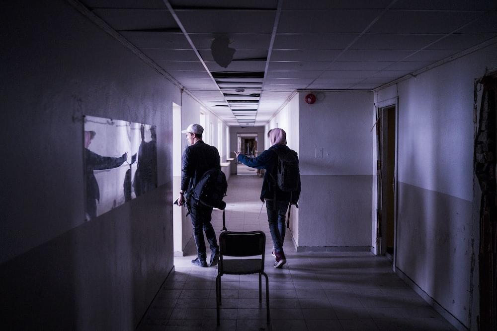 two men walking on corridor