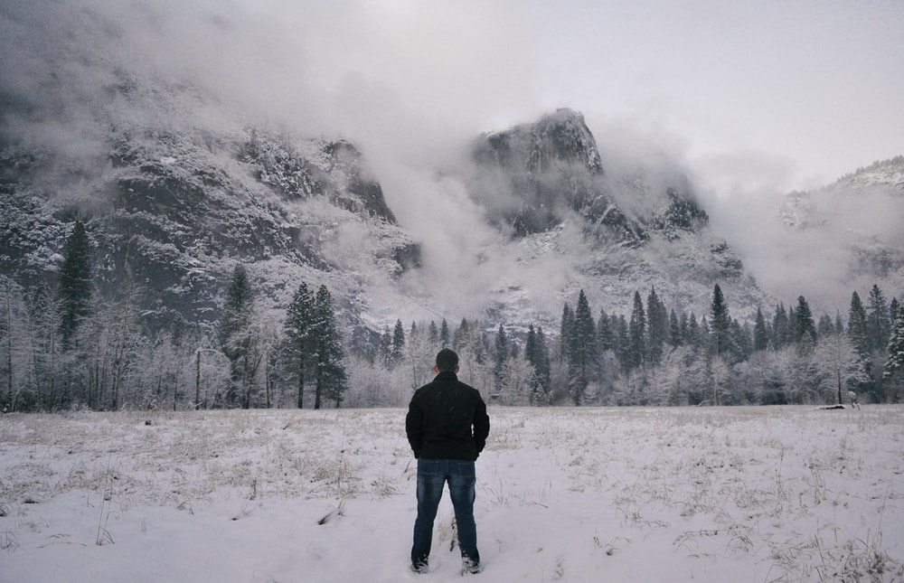 man in black jacket standing on snow covered ground