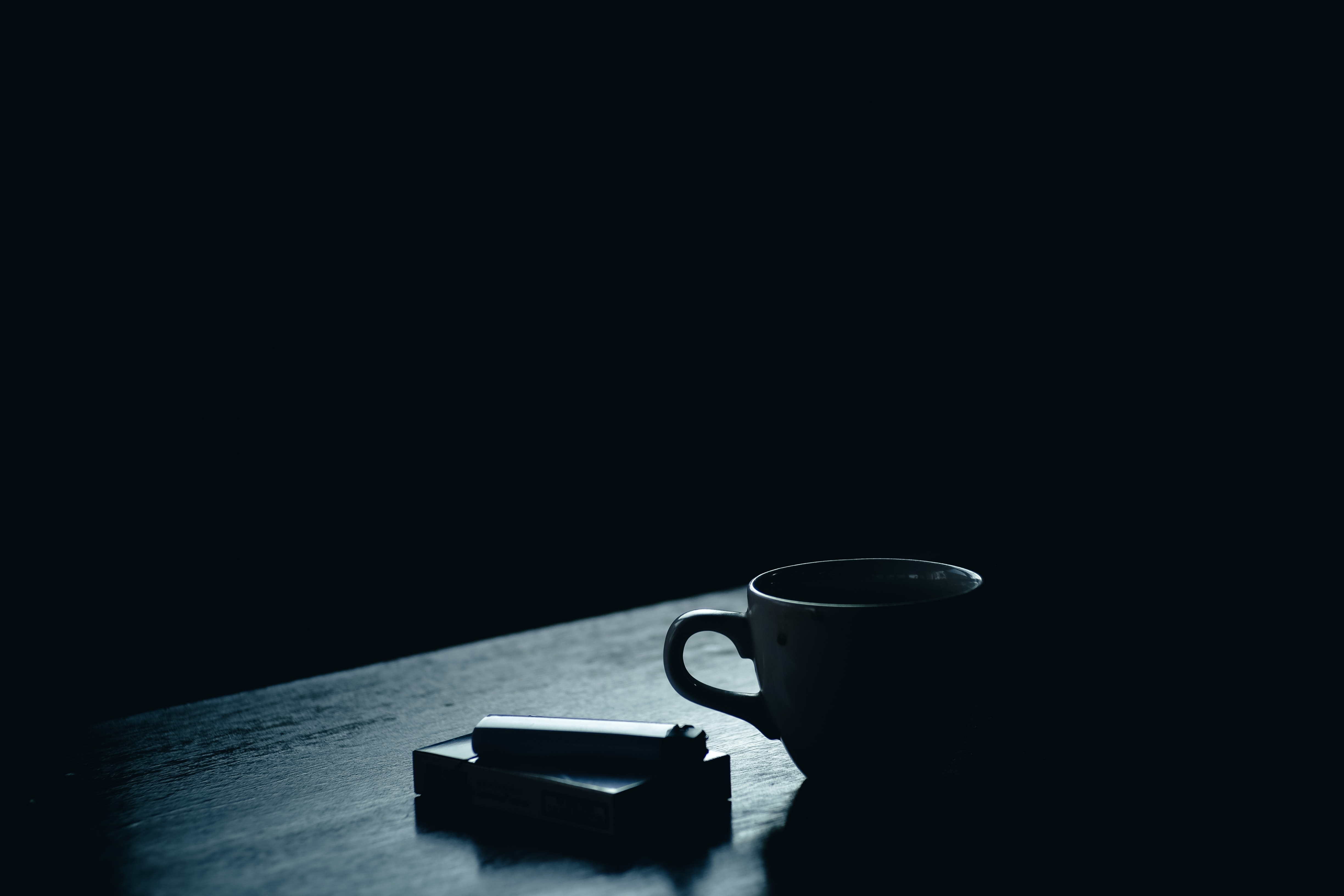 A dim shot of a pack of cigarettes and a lighter next to a teacup