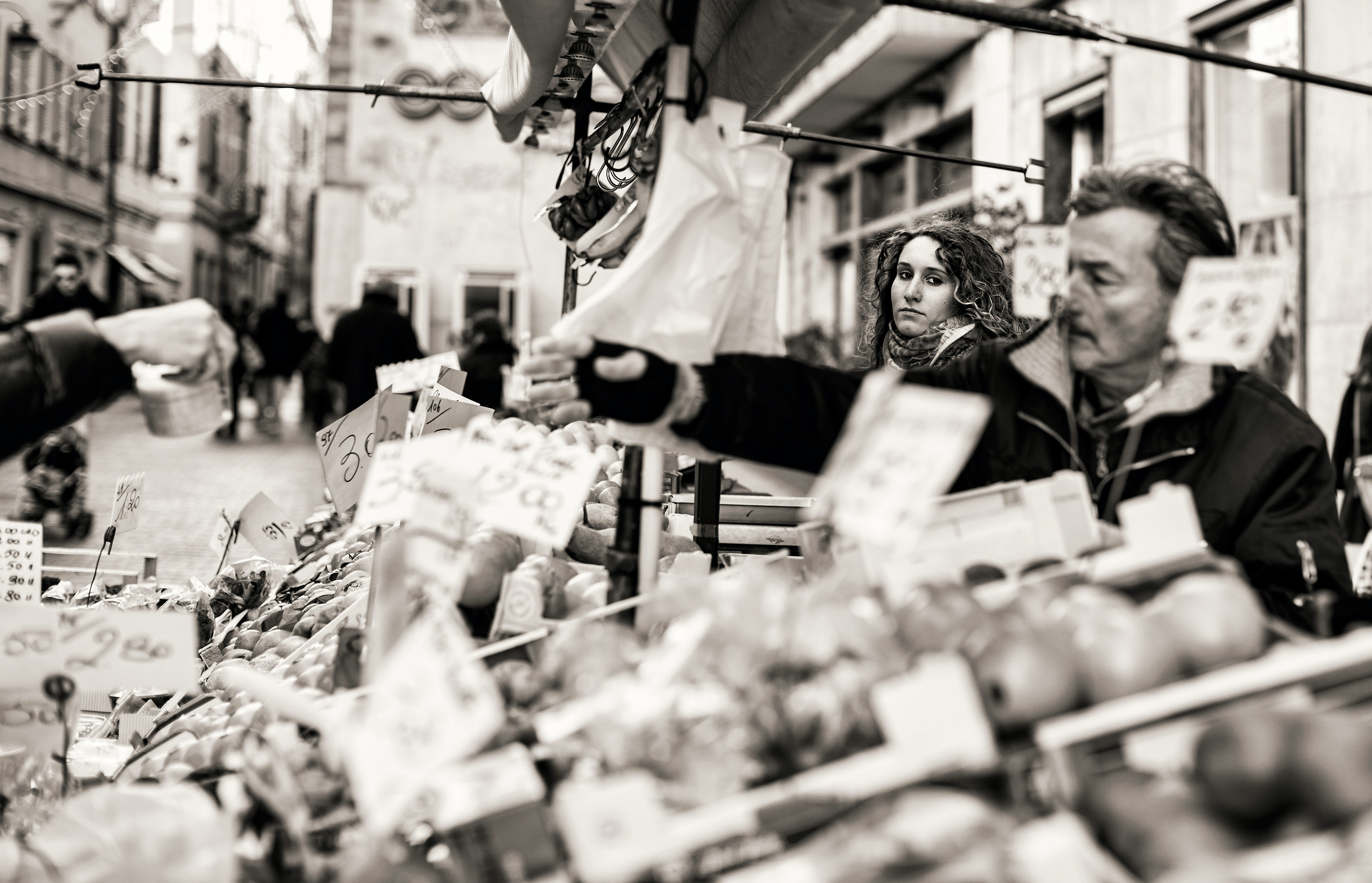 A black-and-white shot of people selecting produce at a market stall