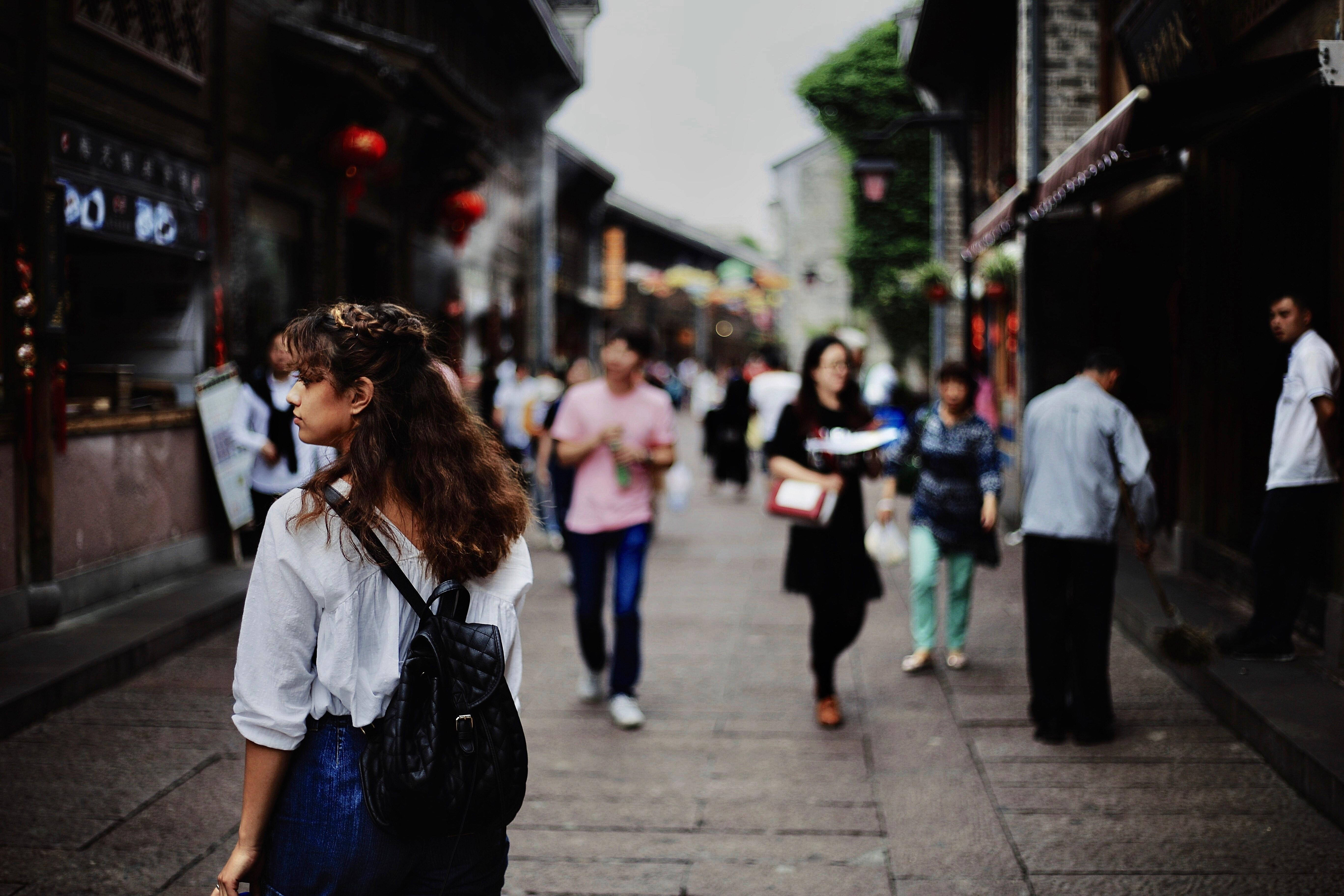 Woman walks through a diverse crowd on a busy city street