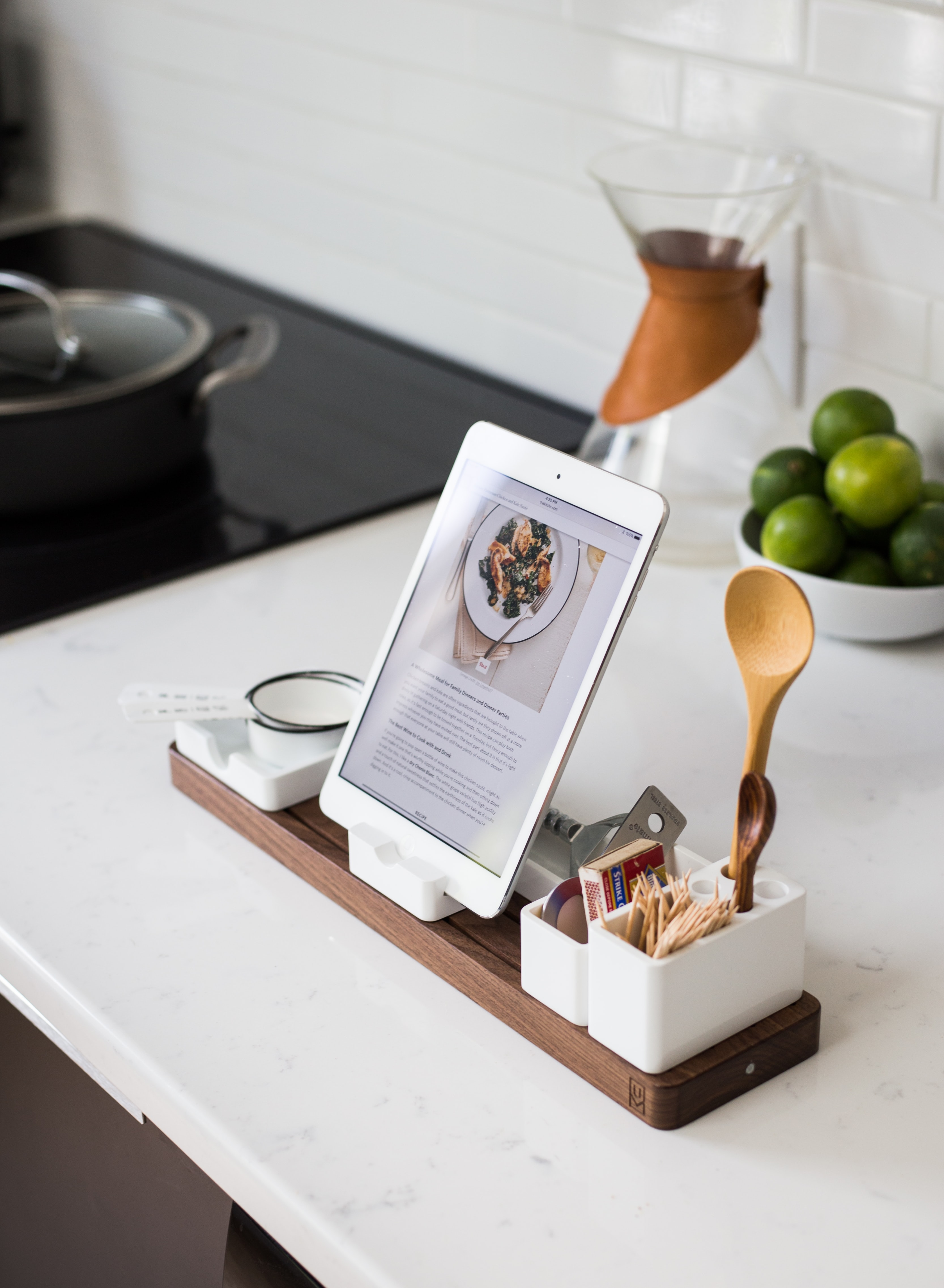 An iPad in a dock surrounded with kitchen utensils in a kitchen
