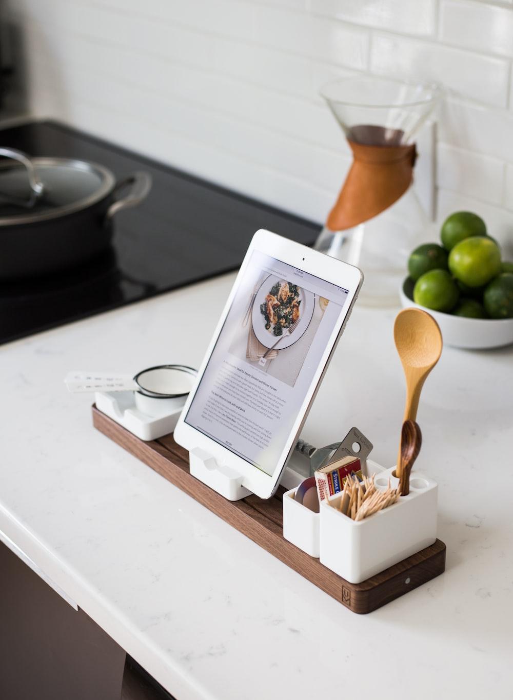 closeup photo of turned on iPad with rack on table