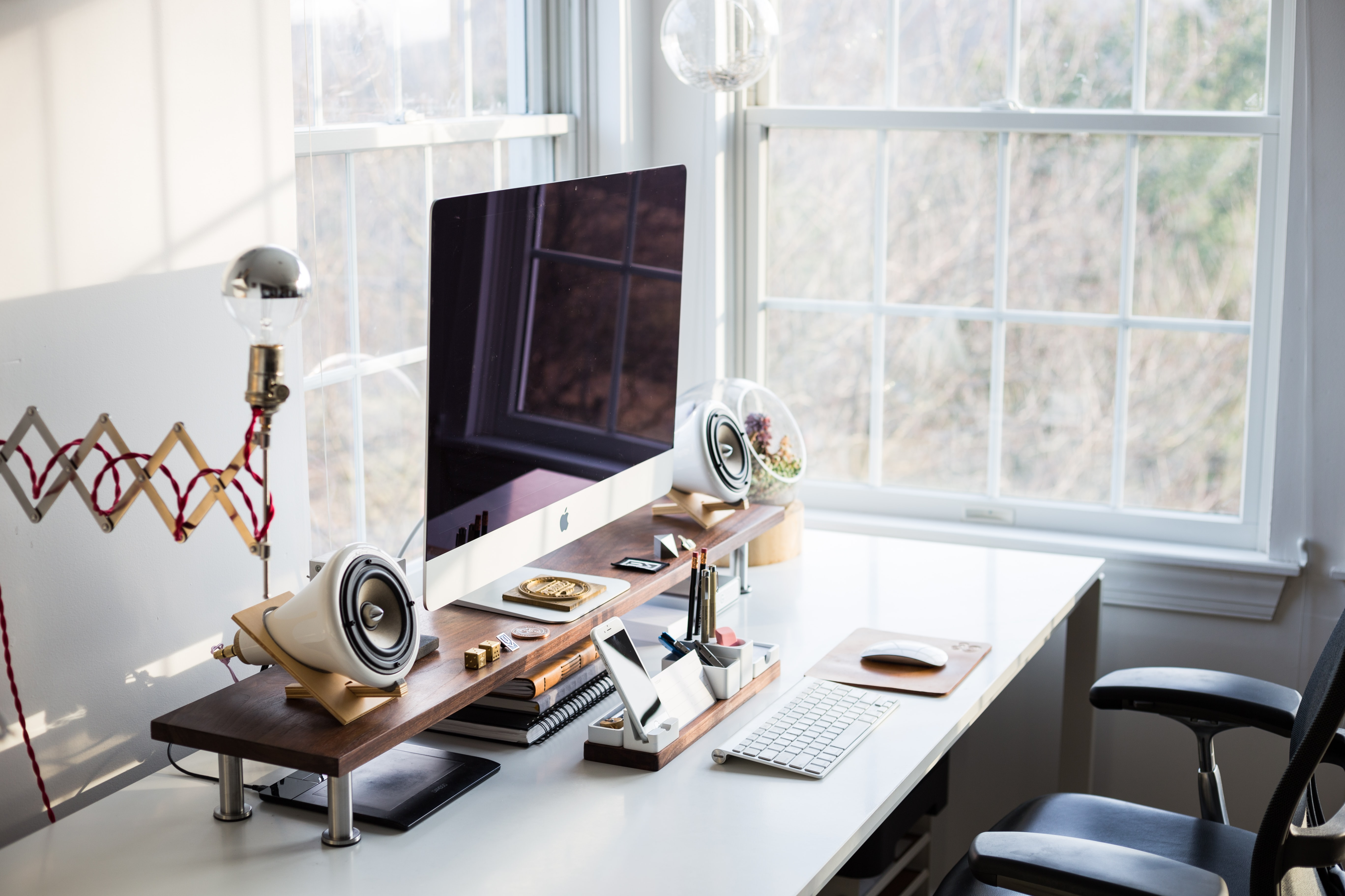 An orderly desk with an iMac and an iPhone in a bright room corner with two windows