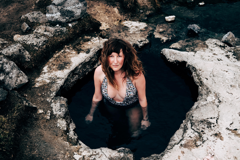 woman in cave wearing one-piece swimsuit looking upward
