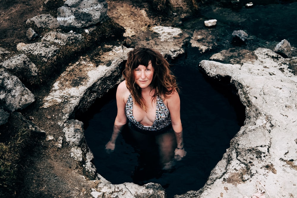 woman in cave wearing one-piece swimsuit looking upward