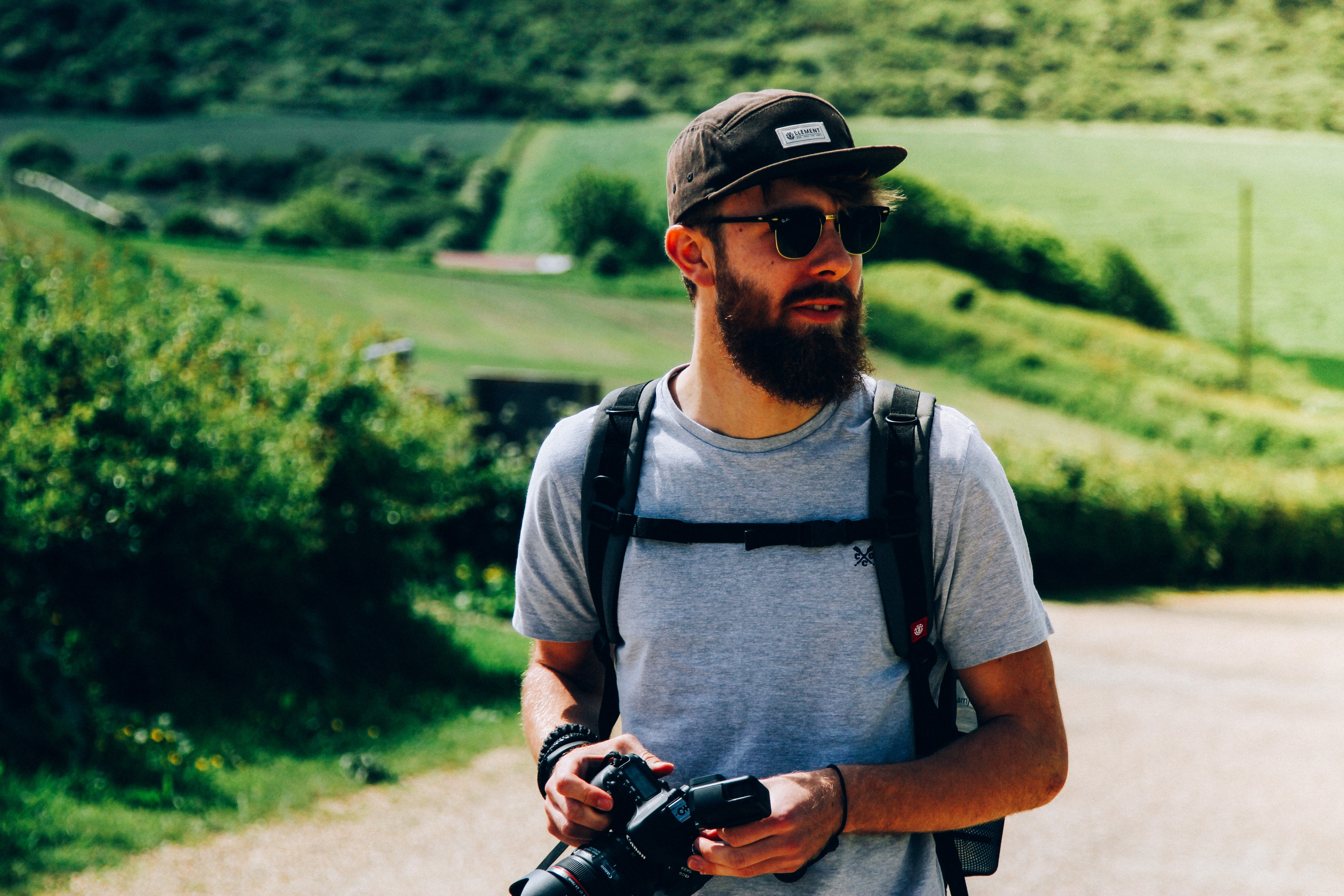 A bearded man wearing a backpack holds a camera outdoors in the Isle of Wight
