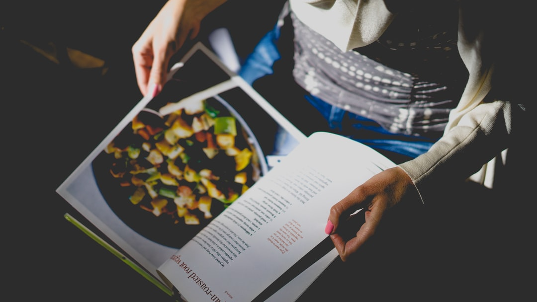 Person reads cookbook recipe