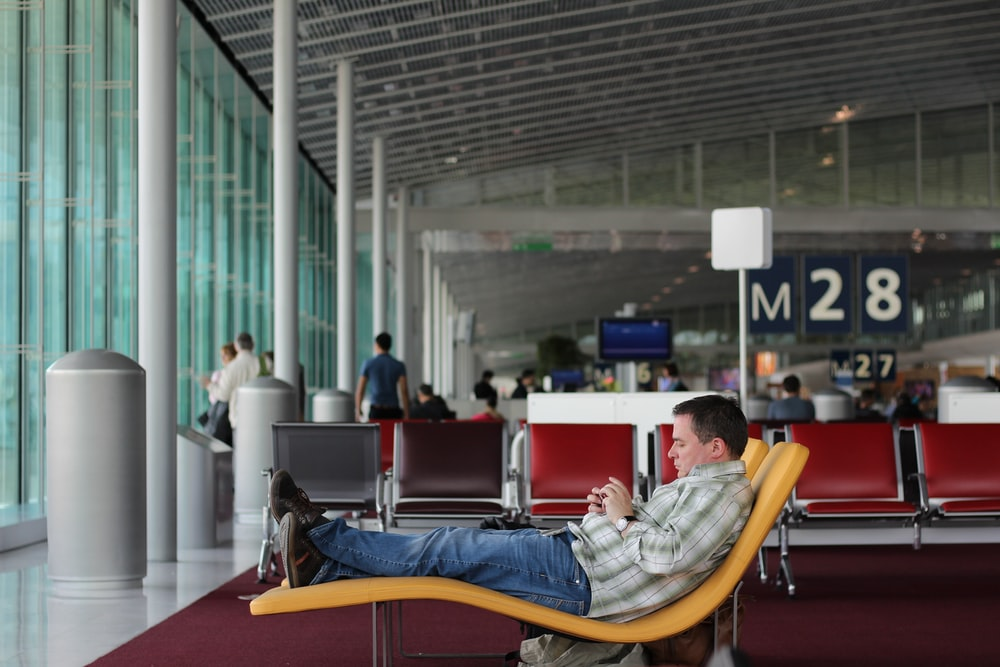 man sitting on airport waiting area