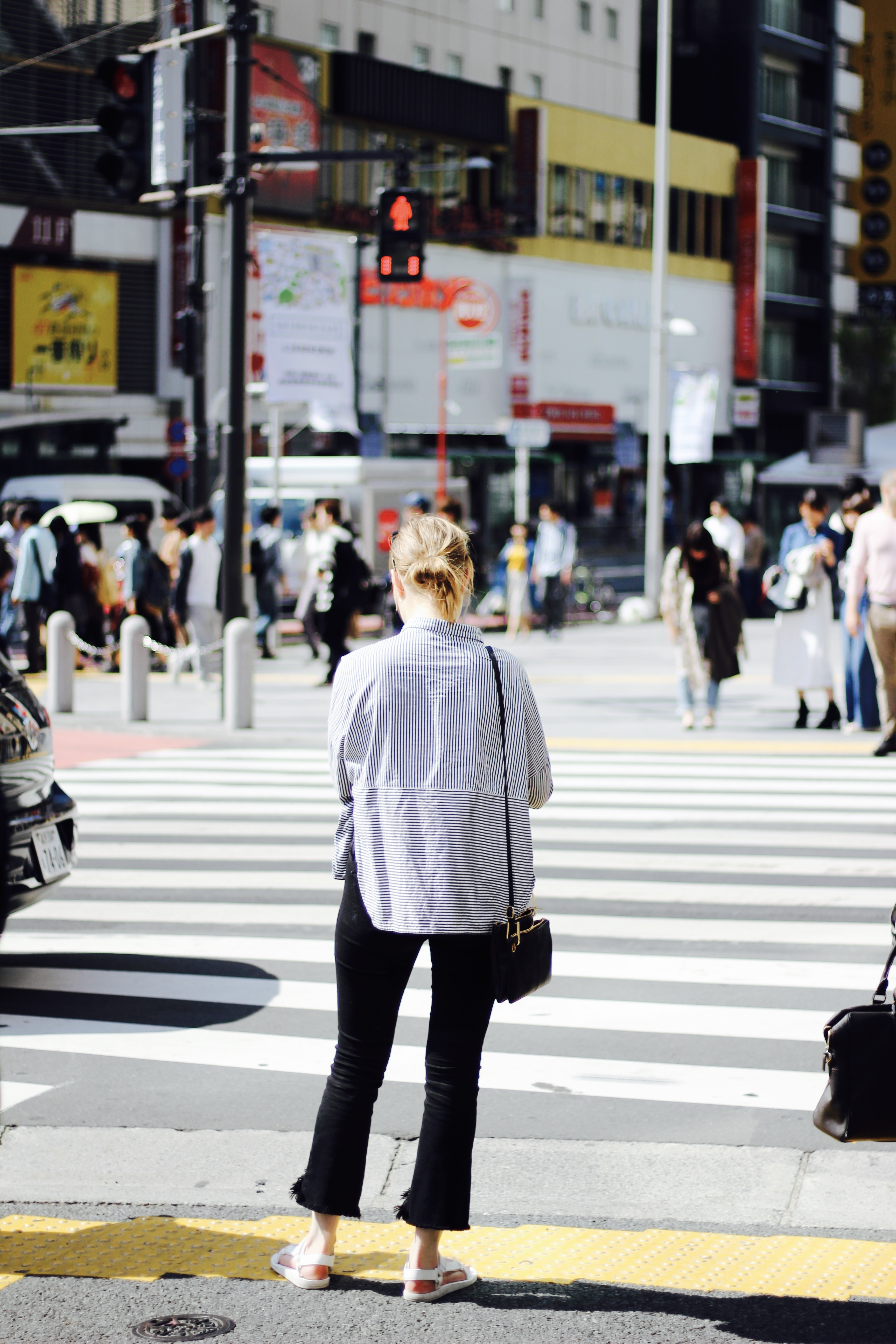 A woman is waiting at the crosswalk for the lights to turn green in Shibuya.