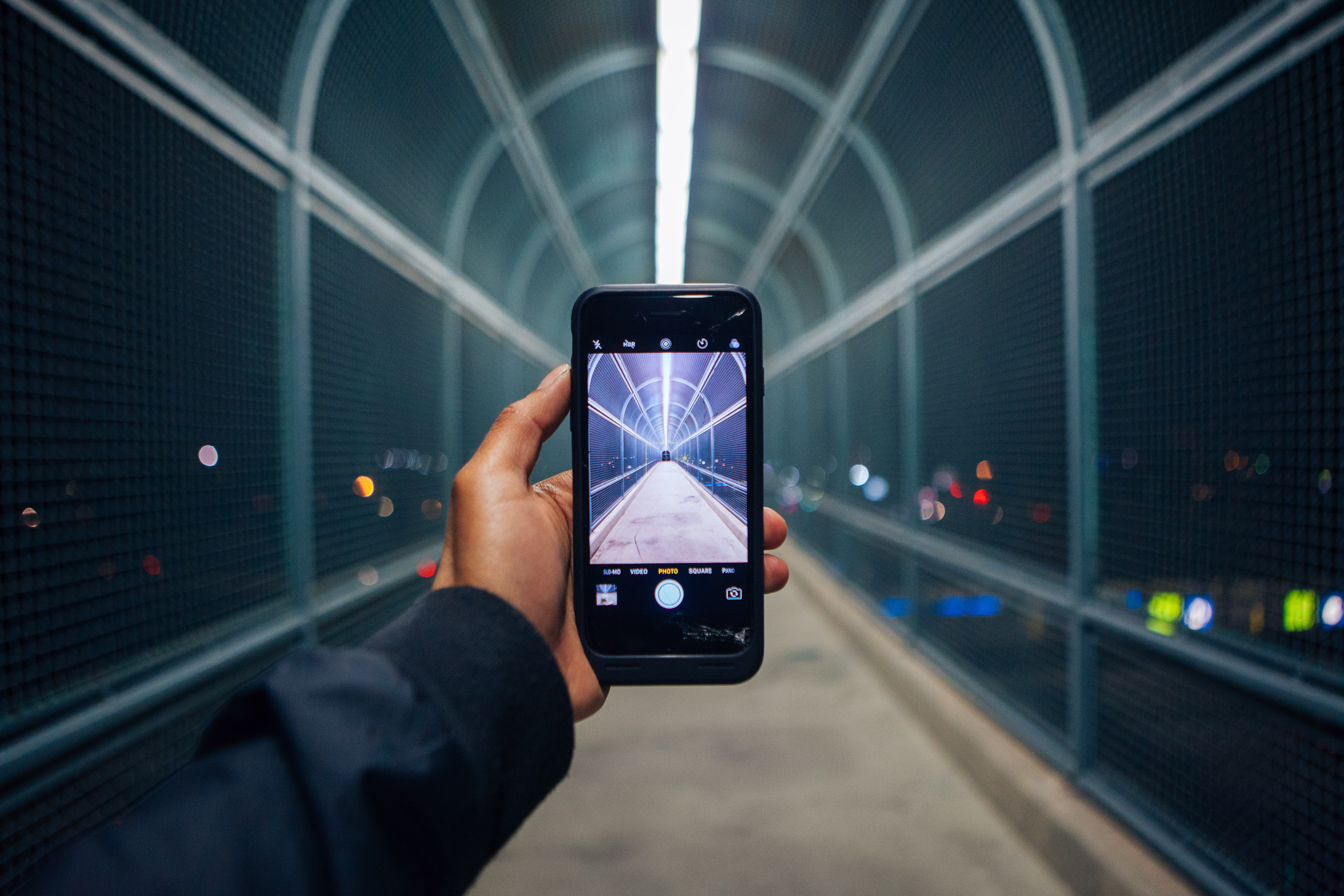 Hand in blue sleeve holding smartphone taking a photograph of a bridge at night