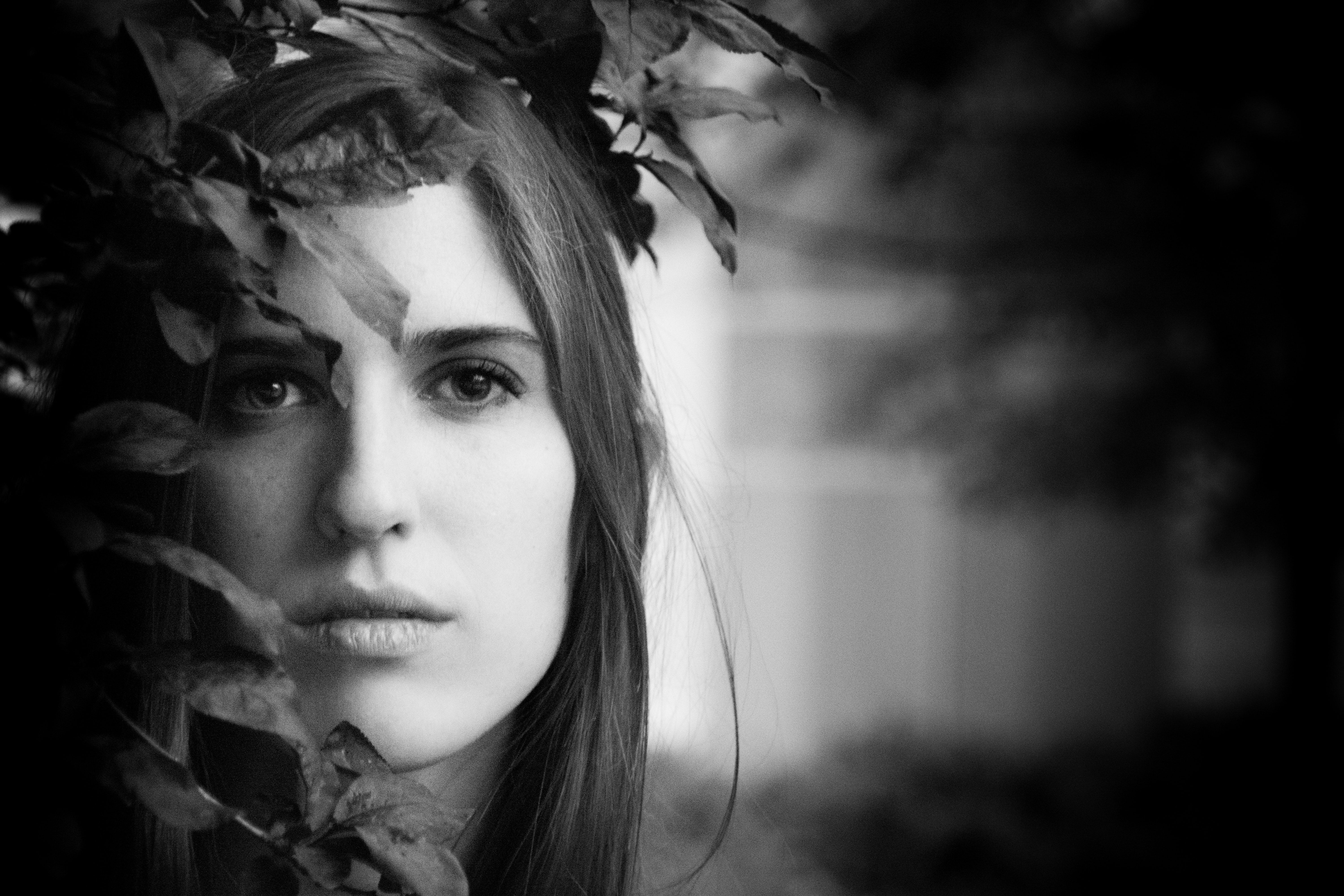 Black and white portrait shot of attractive dark haired woman's head amongst leaves