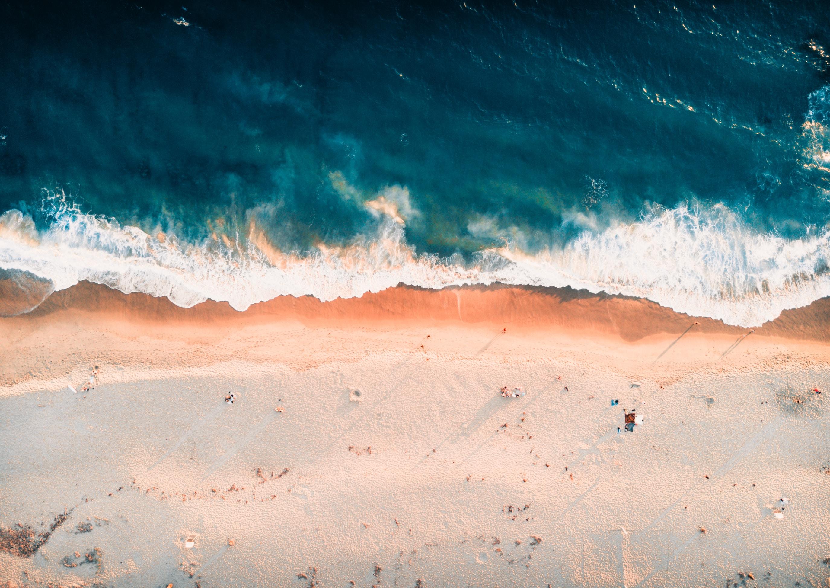 Drone view of the waves splashing on the Laguna Beach sand coastline