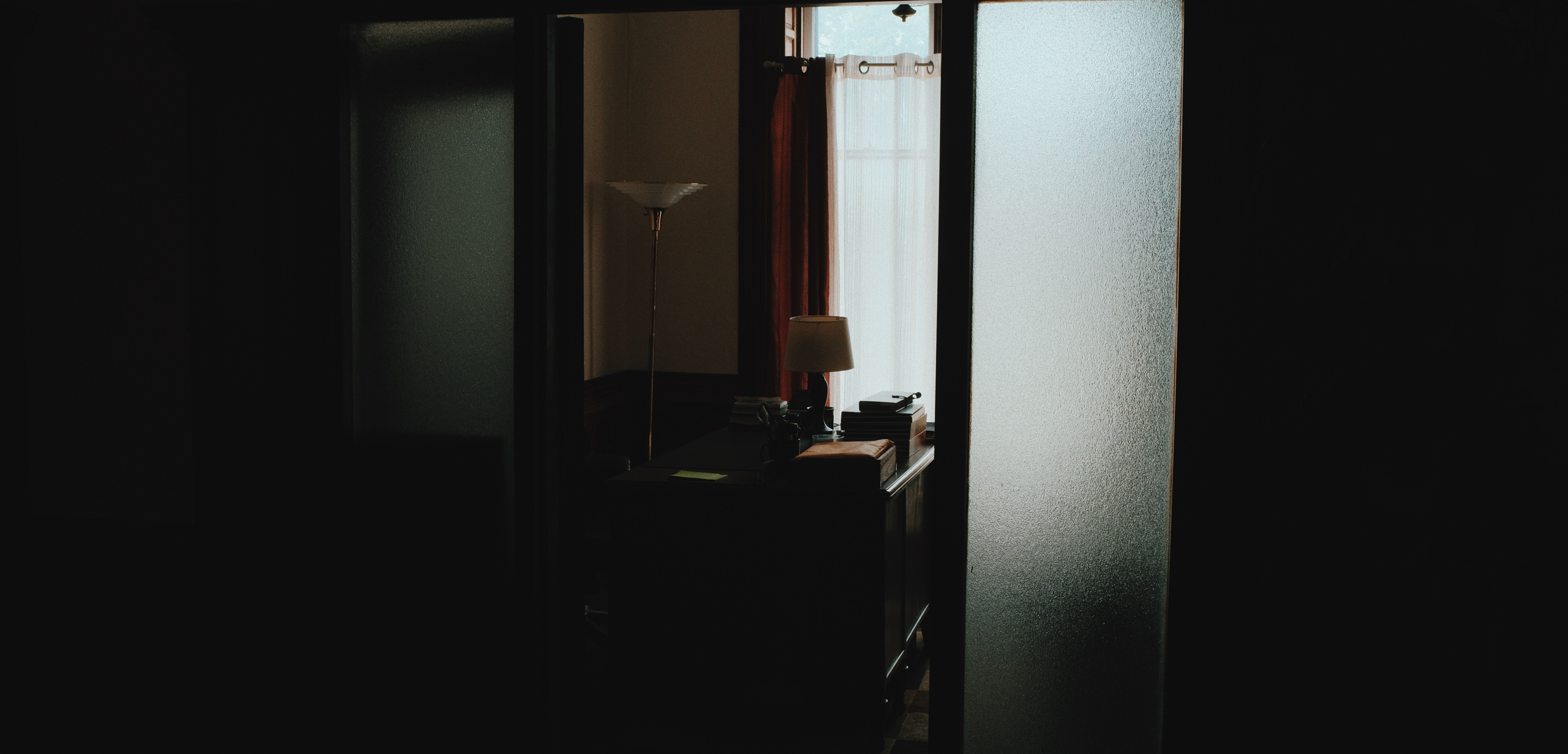 Dark hallway leading to office with desk and lamp