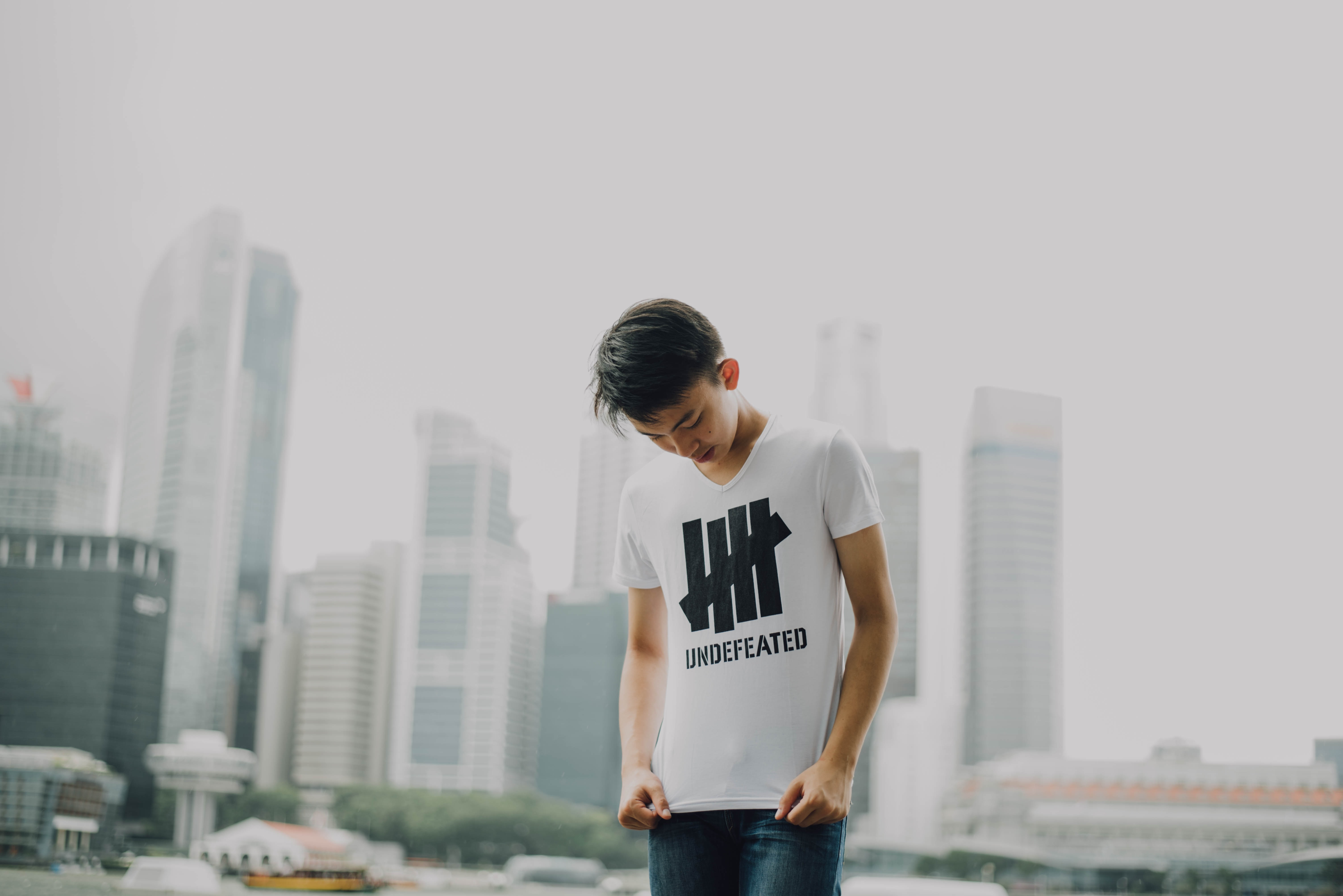 """A person in a white t-shirt reading """"UNDEFEATED"""" stands before an urban skyline"""