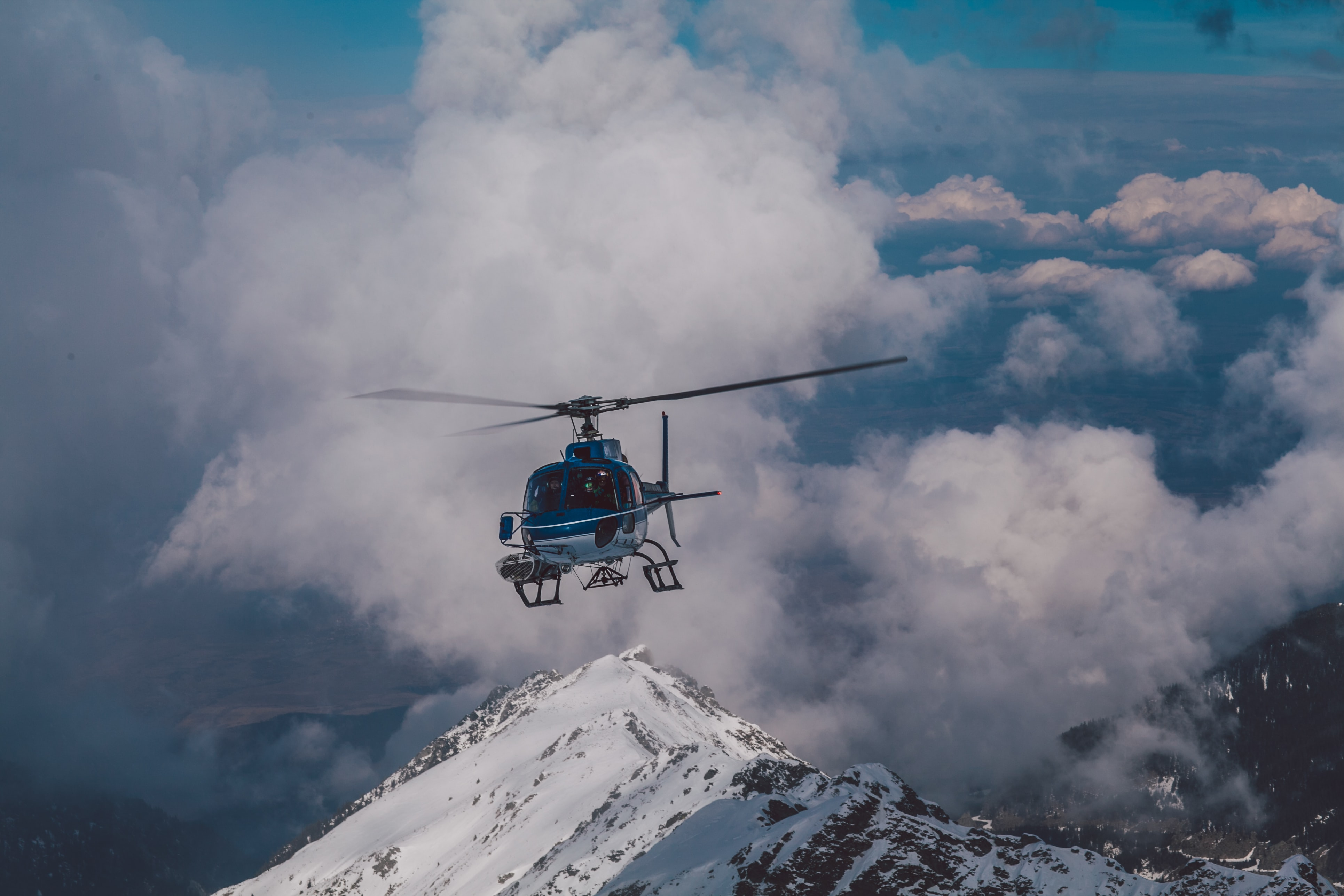 A blue helicopter is flying away from clouds and a snowcapped mountain