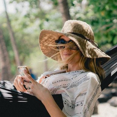 woman lying on black hammock while holding phone