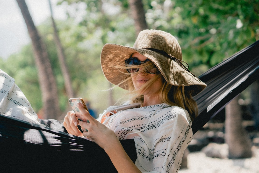 A woman with windswept hair, a hat, and sunglasses holds an iPhone in a hammock outdoors