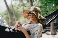 woman lying on black hammock while holding phone