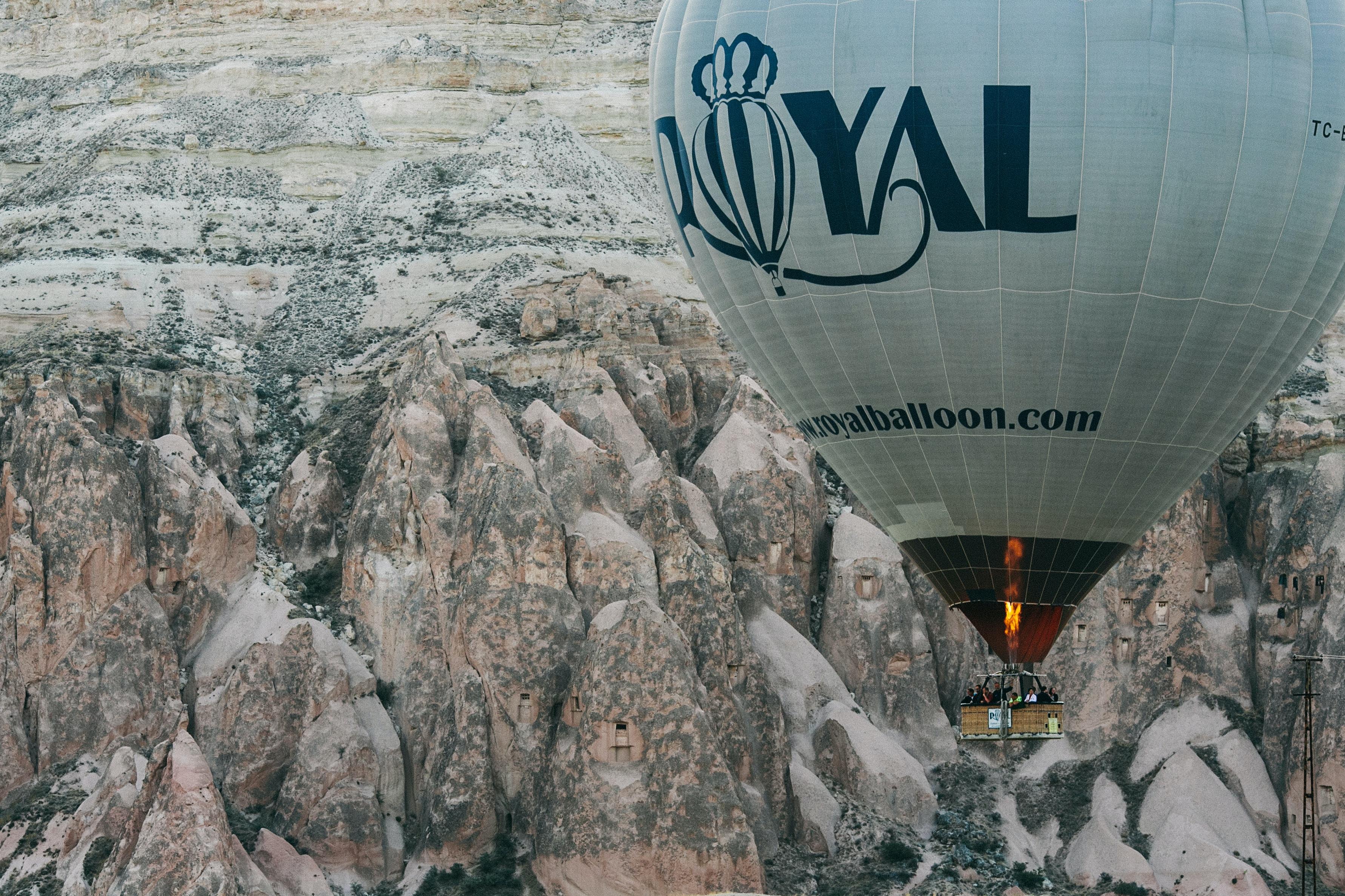 white and black Royal hot air balloon near mountain