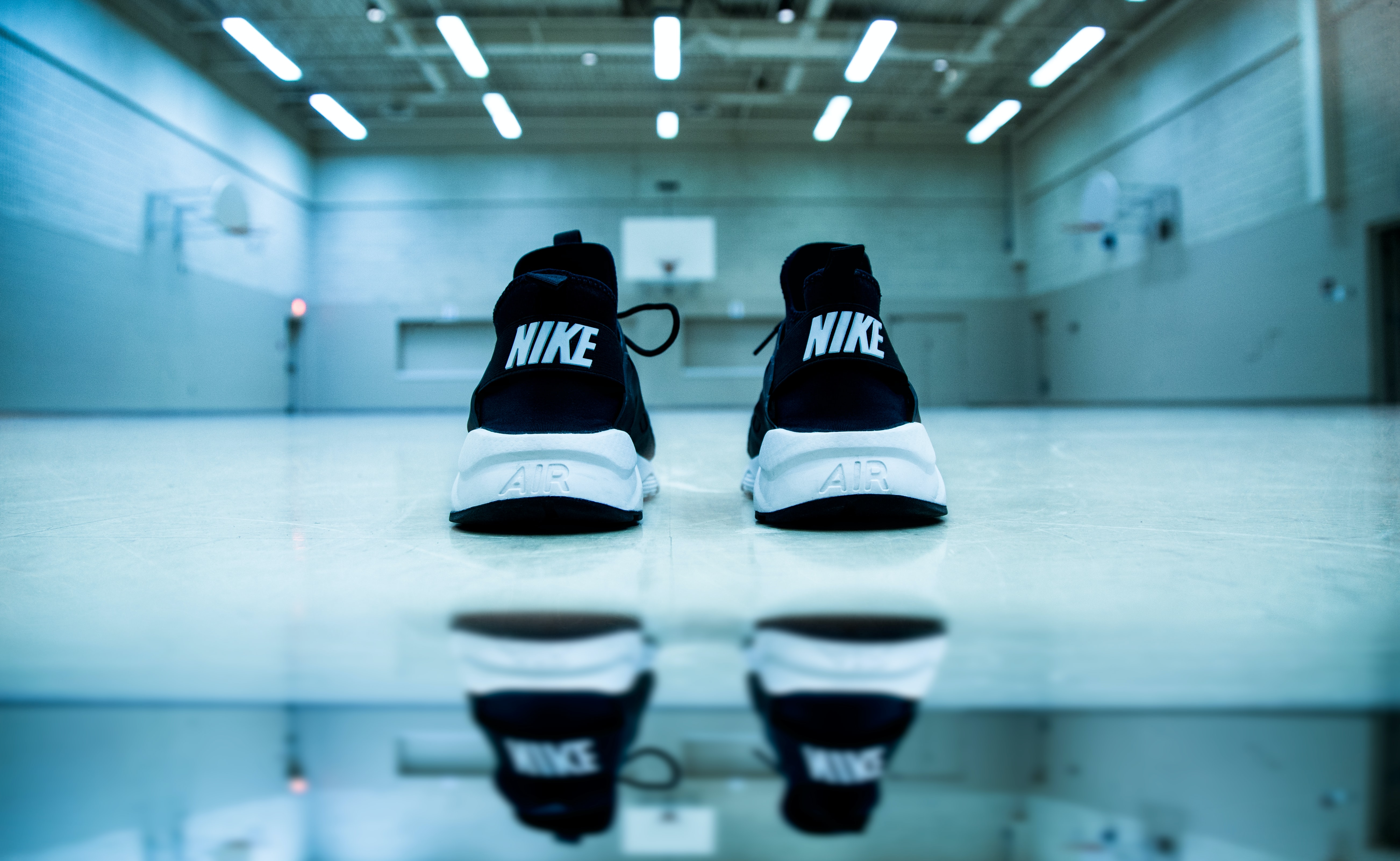 Black Nike sneakers are reflected in a reflective surface underneath fluorescent lights