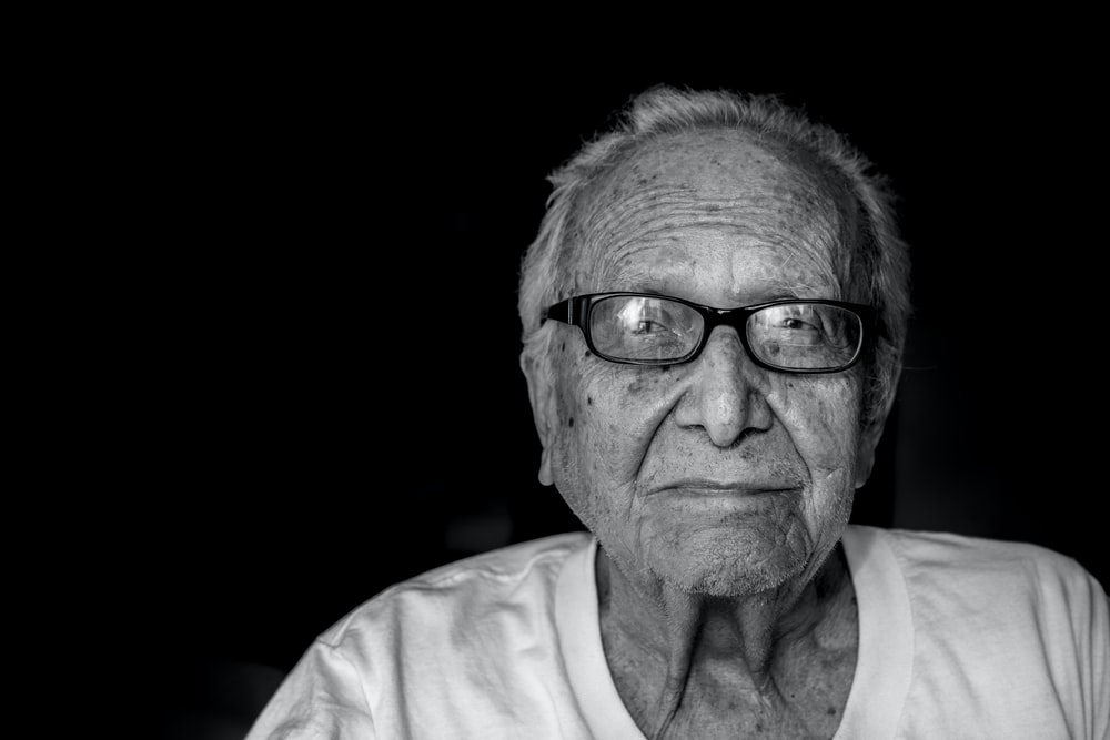 grayscale photography of man wearing shirt and eyeglasses