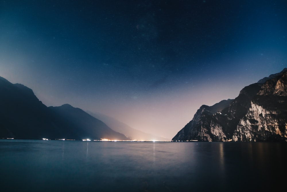 horizon scenery of mountain and sea during nighttime