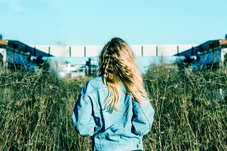 woman wearing blue denim jacket standing on grass field