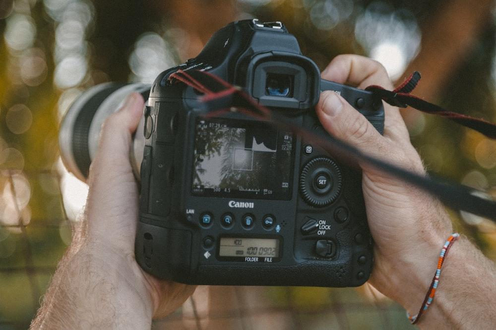 pessoa segurando câmera DSLR