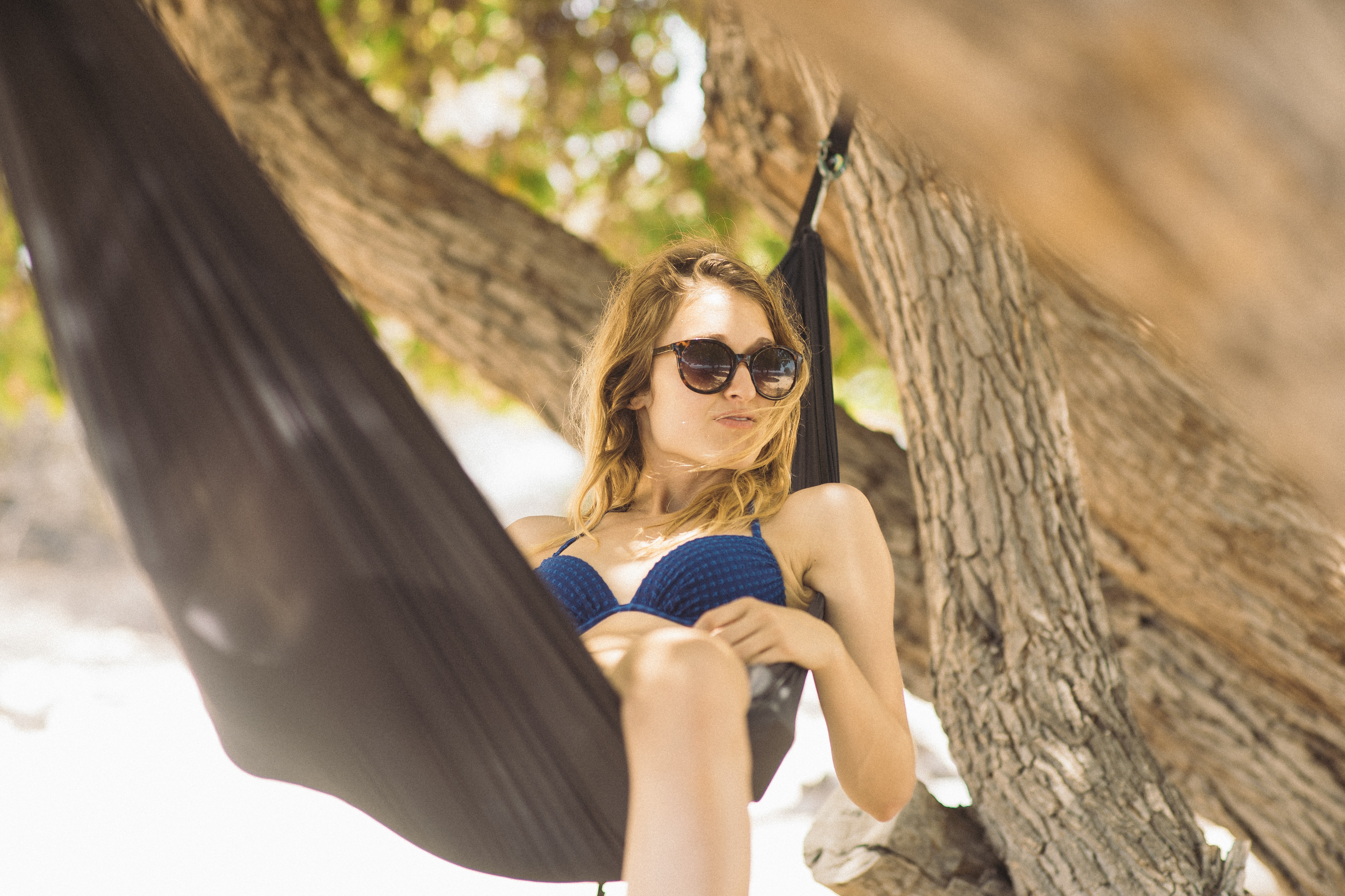 woman in blue bikini lying on black hammock