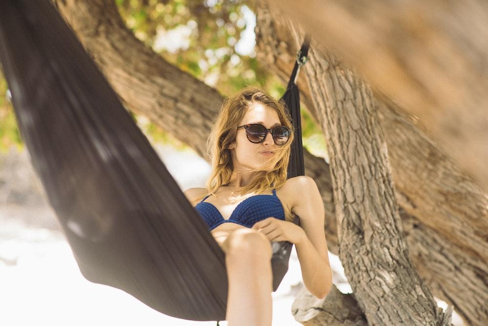 woman in blue bikini lying on black hammock