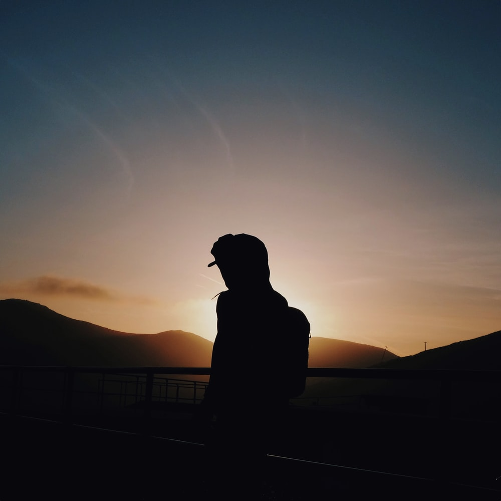 silhouette of man leaning on rails
