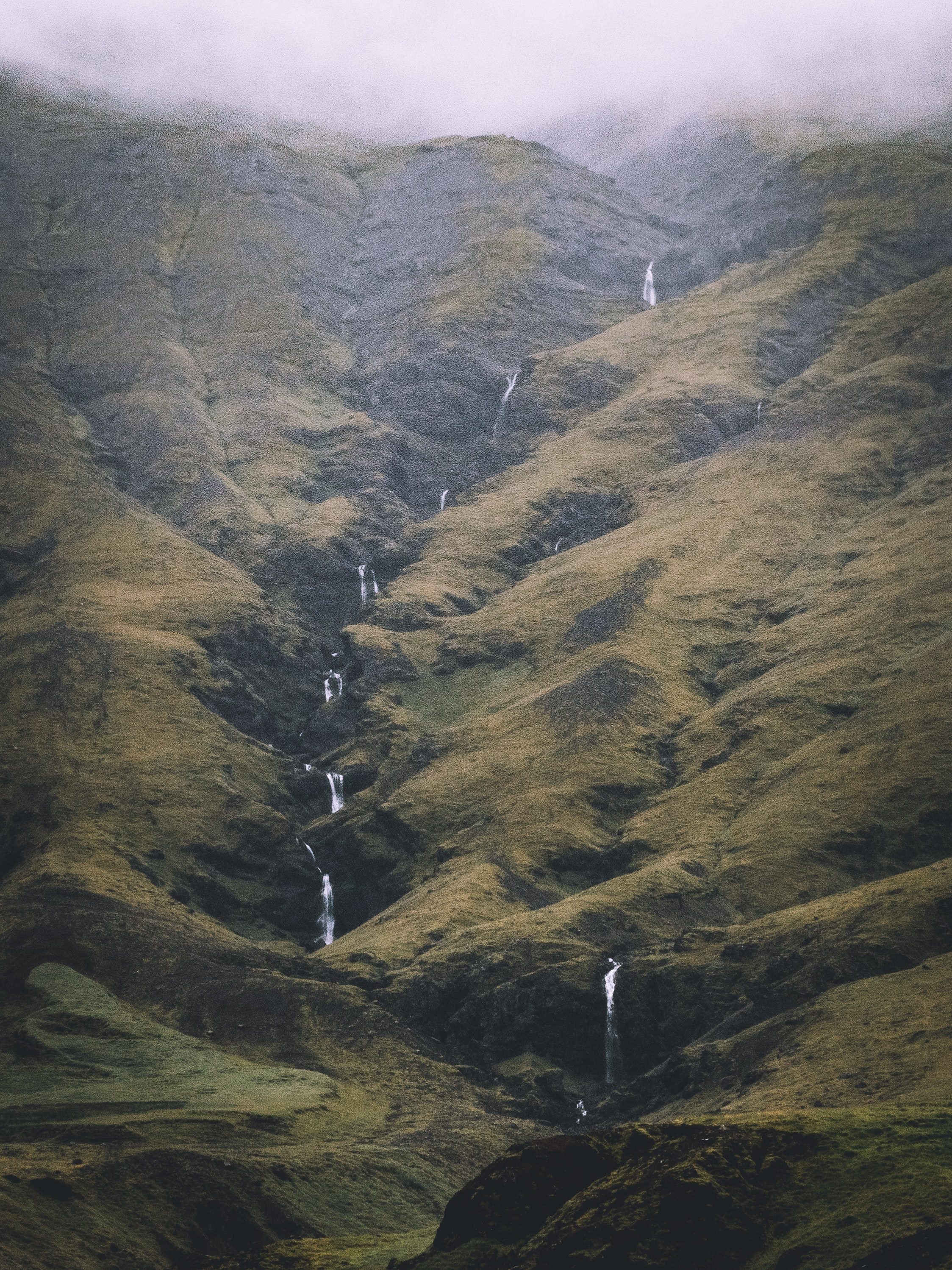 Line of waterfalls in the green, grassy mountains of Iceland