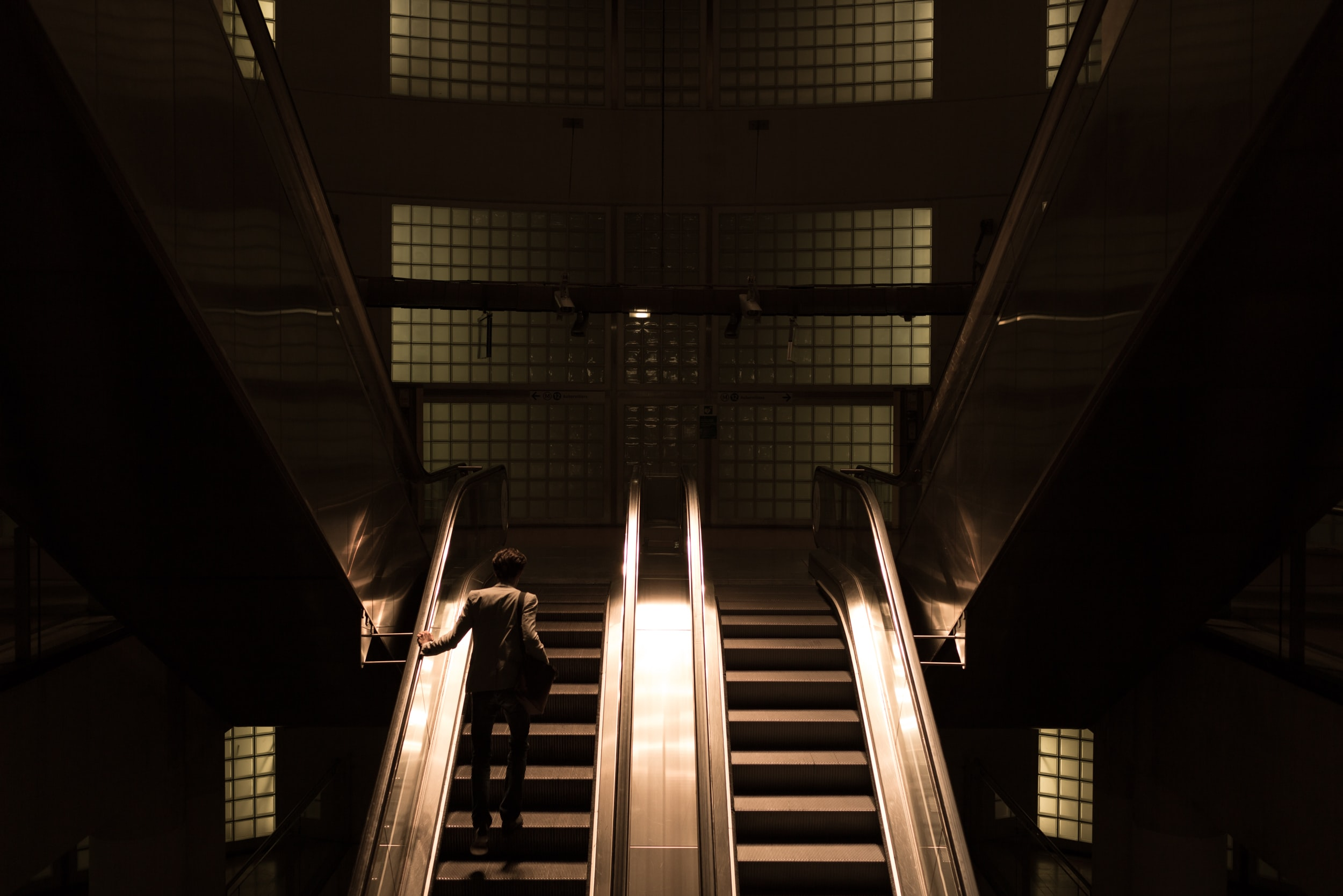 A shadowy shot of a man riding up a pair of escalators in the subway