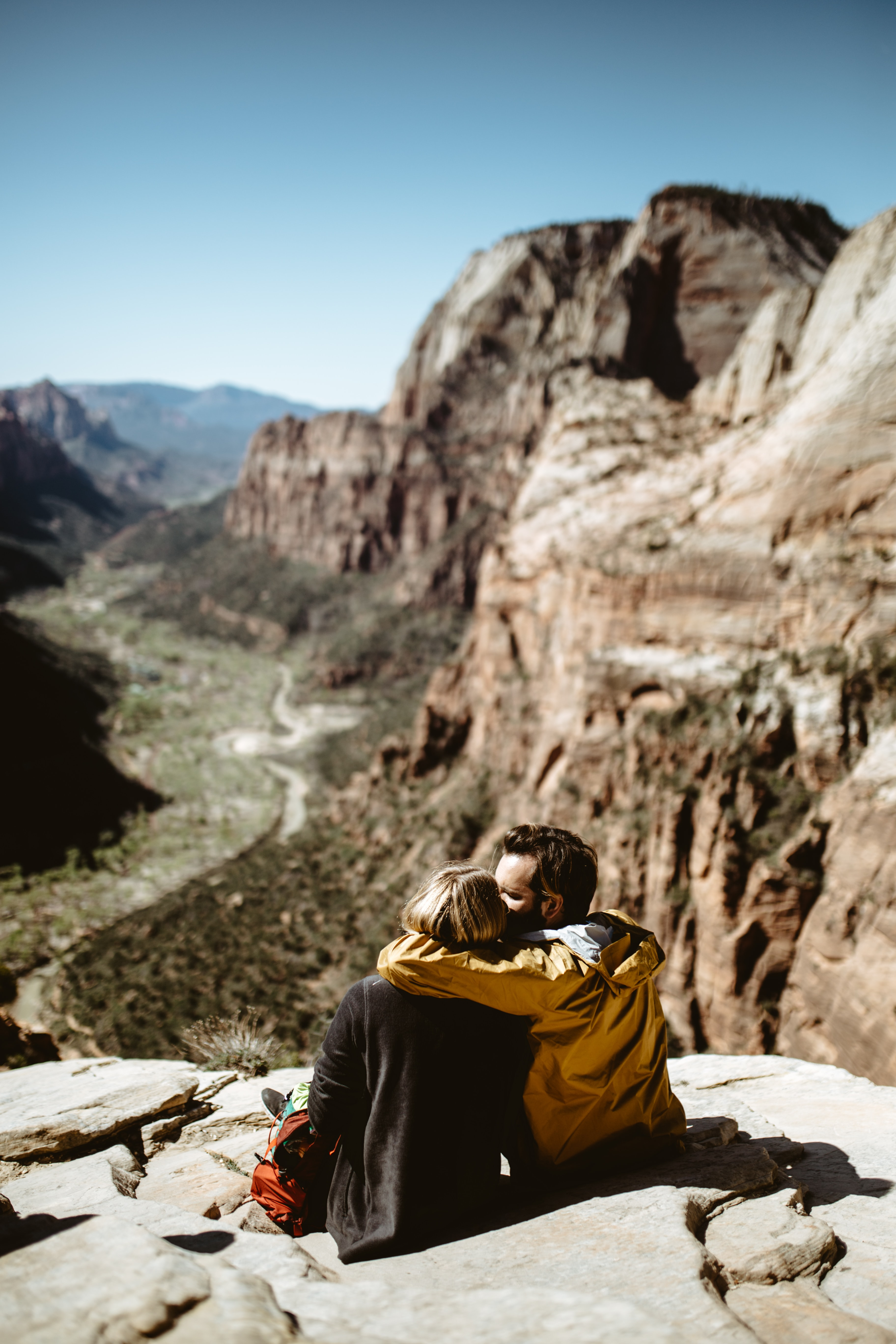 selective focus photography of couple sitting on rock fall under sunlight