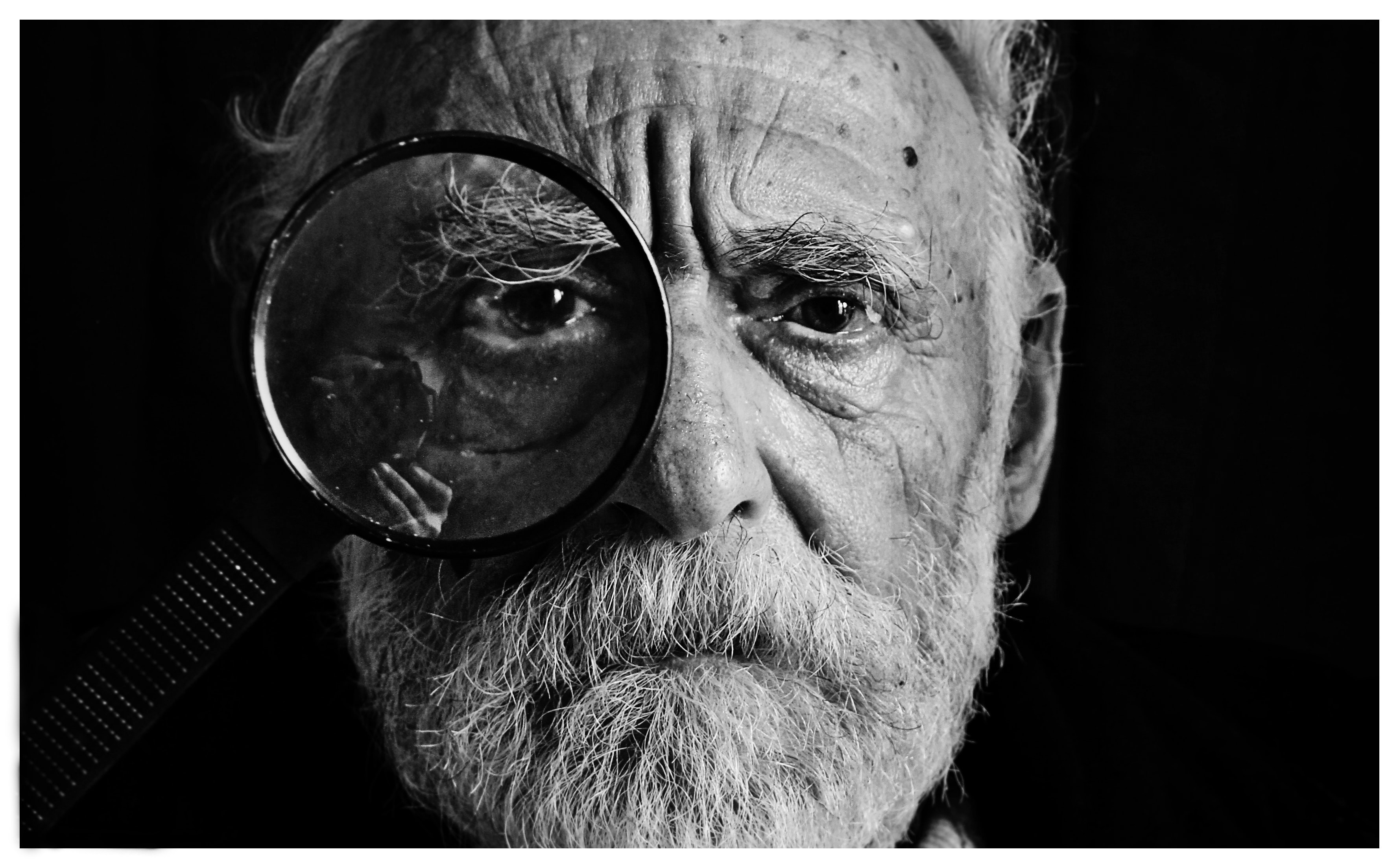 A portrait of an old man with a beard looking through a magnifying glass.
