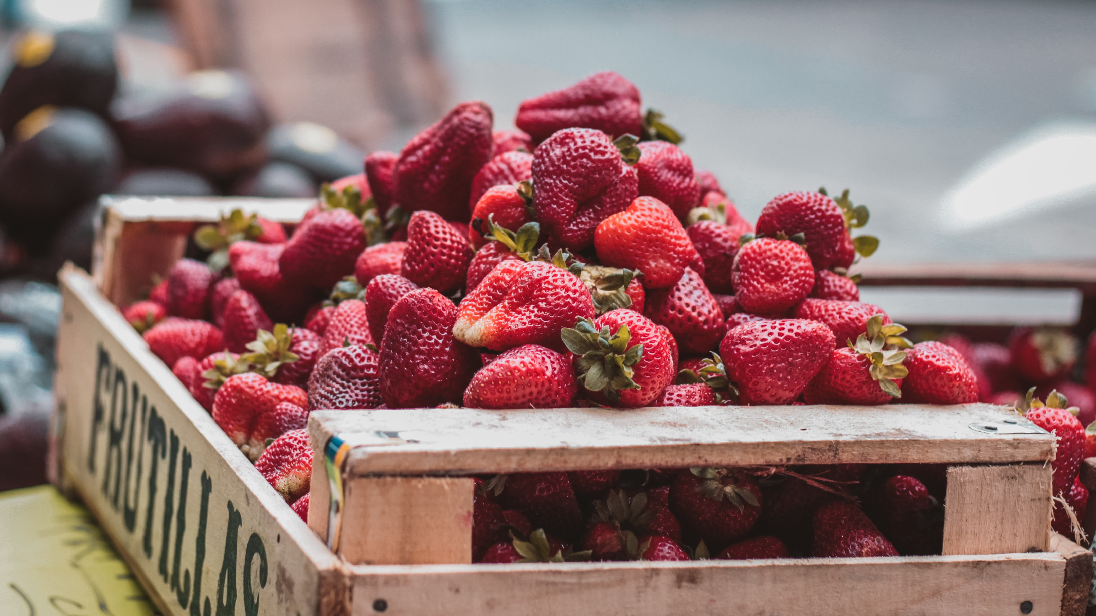 Crate overflowing with fresh red strawberries at the market