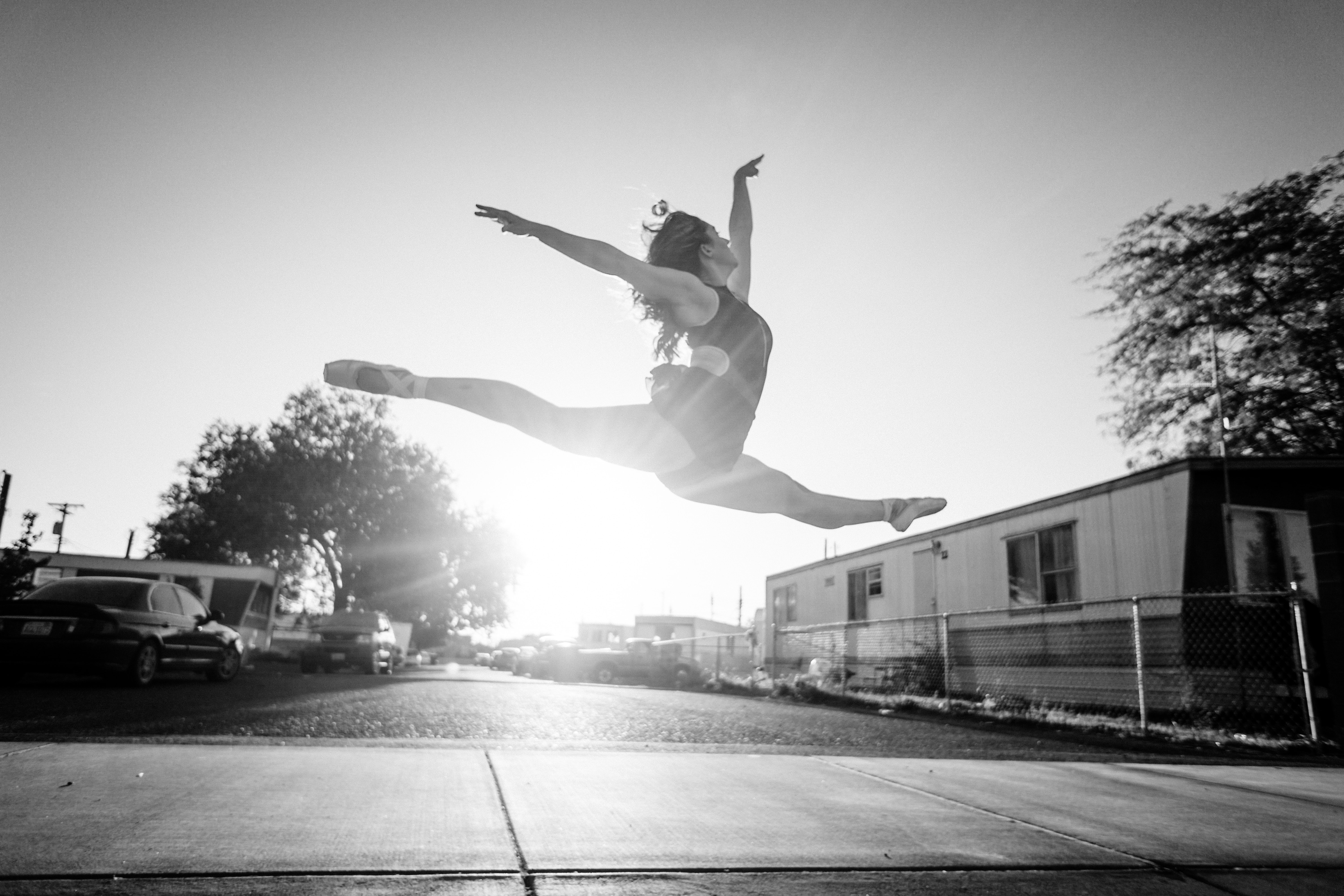 Black and white shot of a female ballet dancer in a split in midair as sun shines in the distance