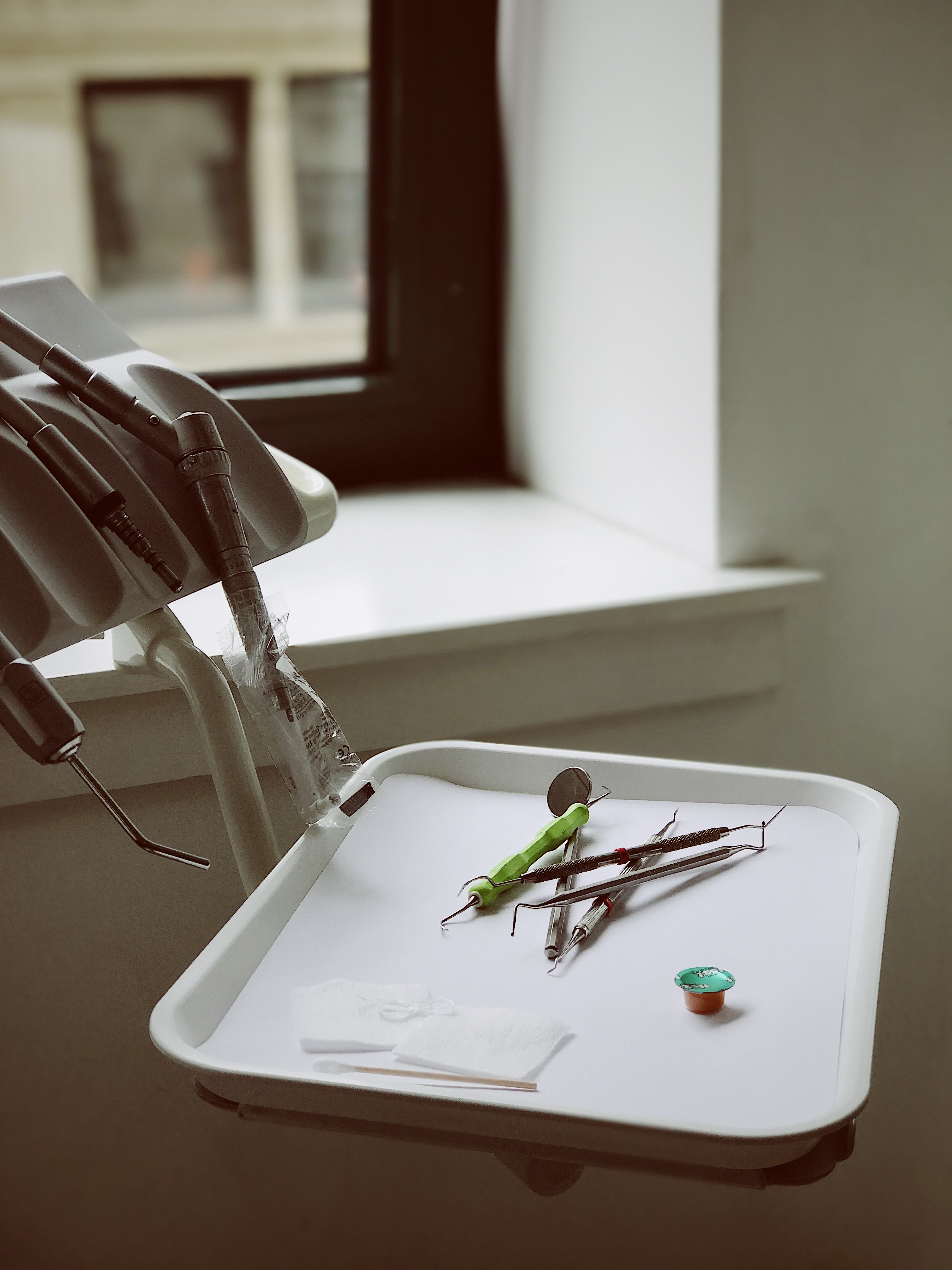 Dentist tools on white tray near window and white wall