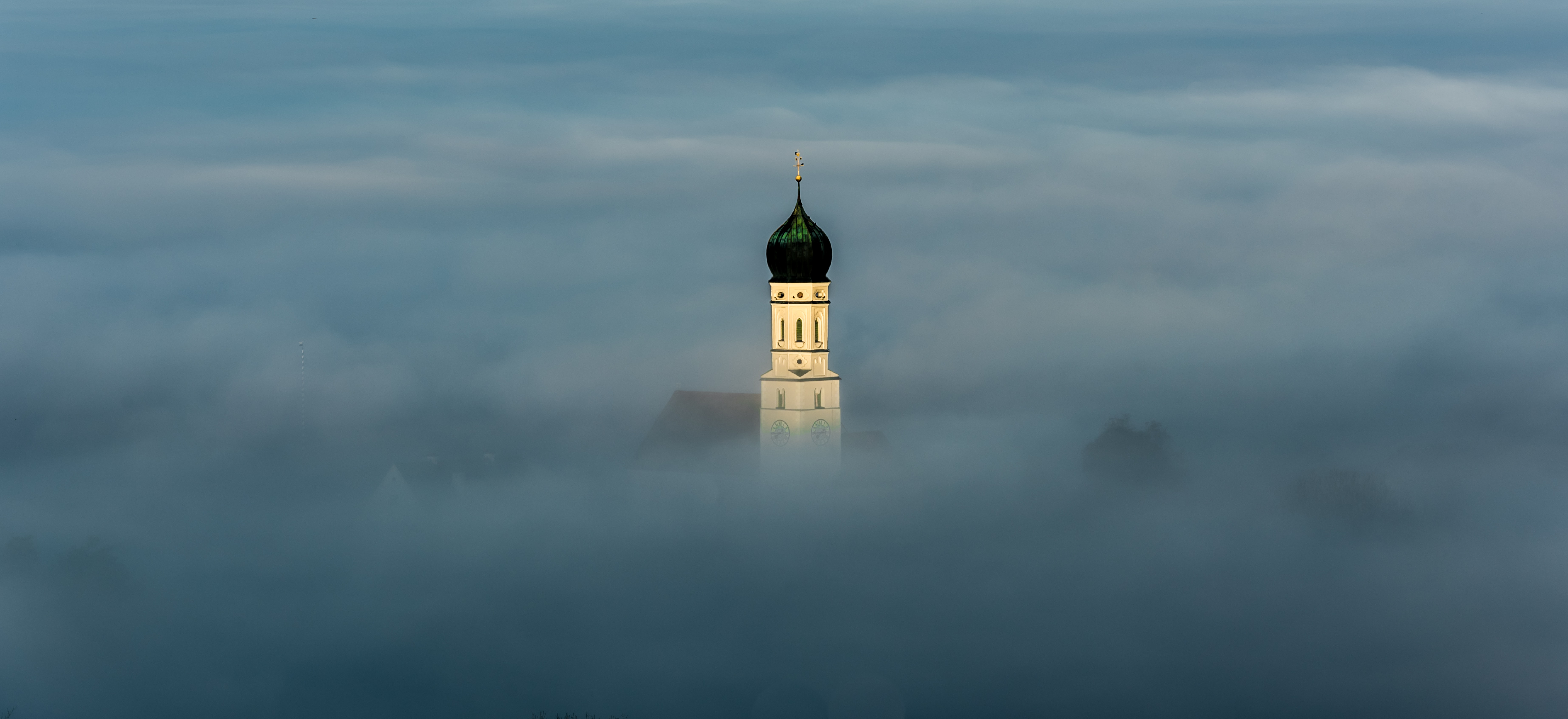 Top of a historic building in Bavaria breaks through the clouds