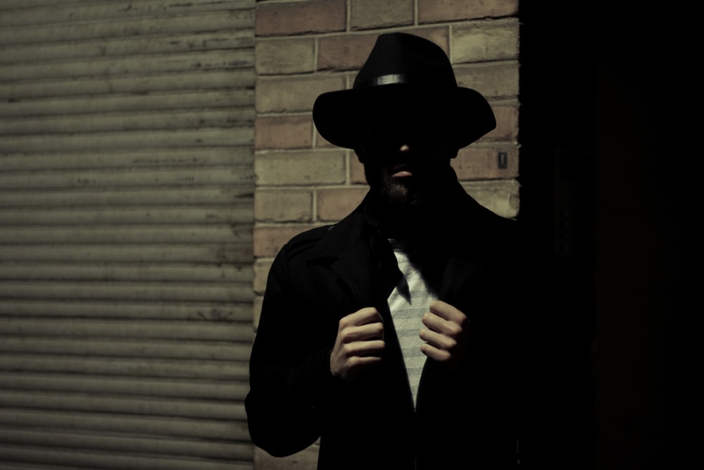 man wearing black fedora hat and black suit jacket