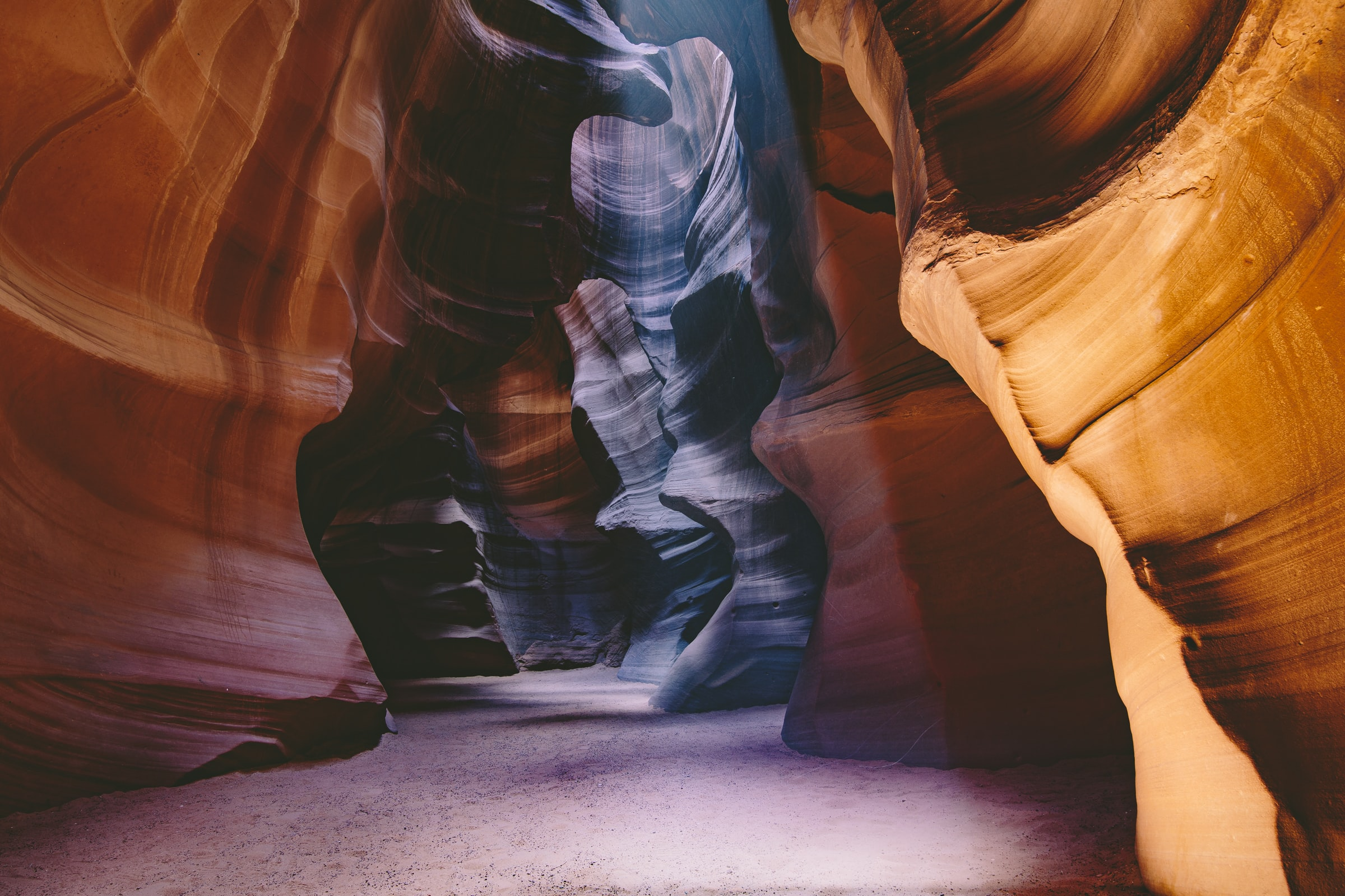 Sunlight shines inside Antelope Canyons casting shadows on the curved walls