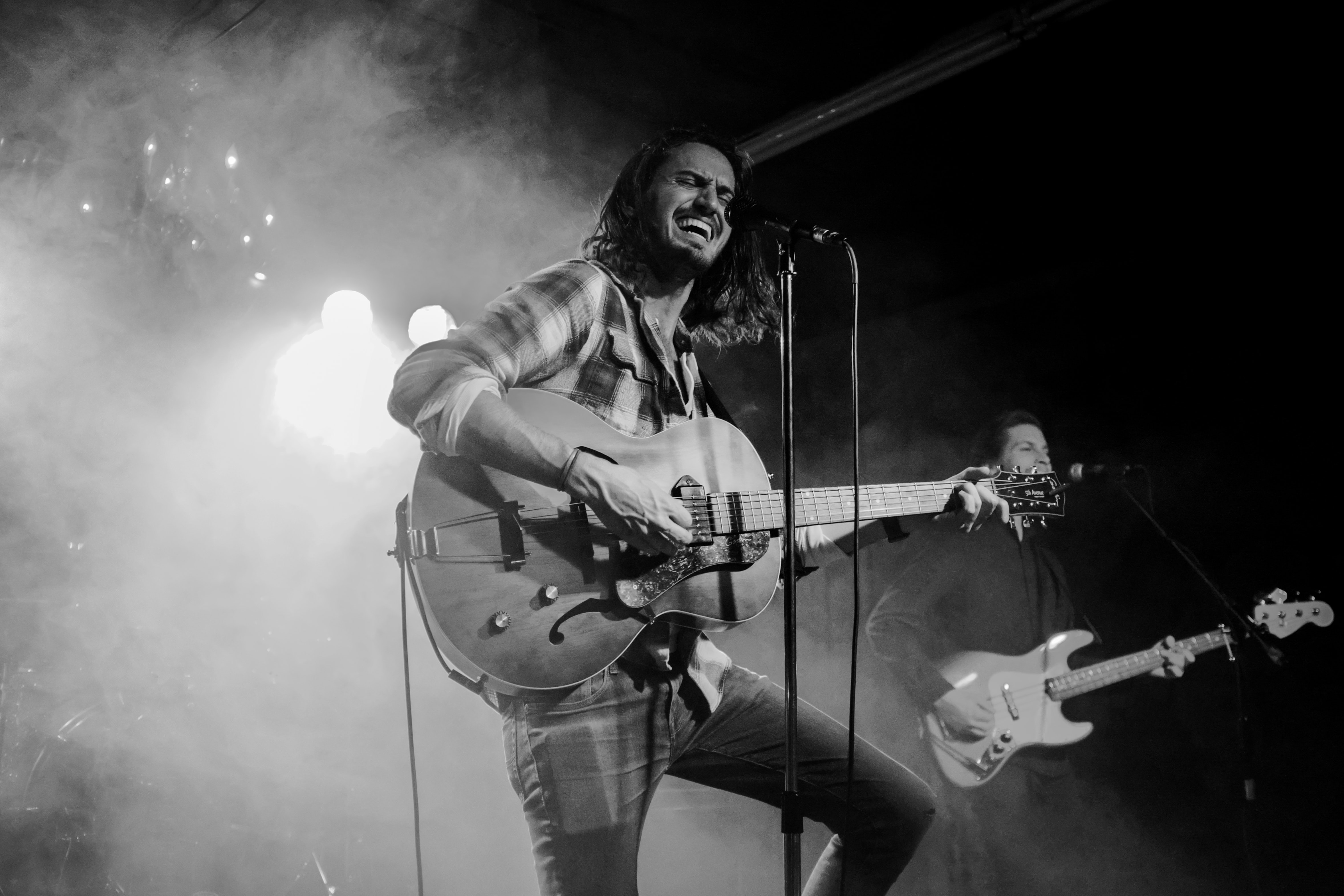grayscale photography of man about to sing while playing guitar