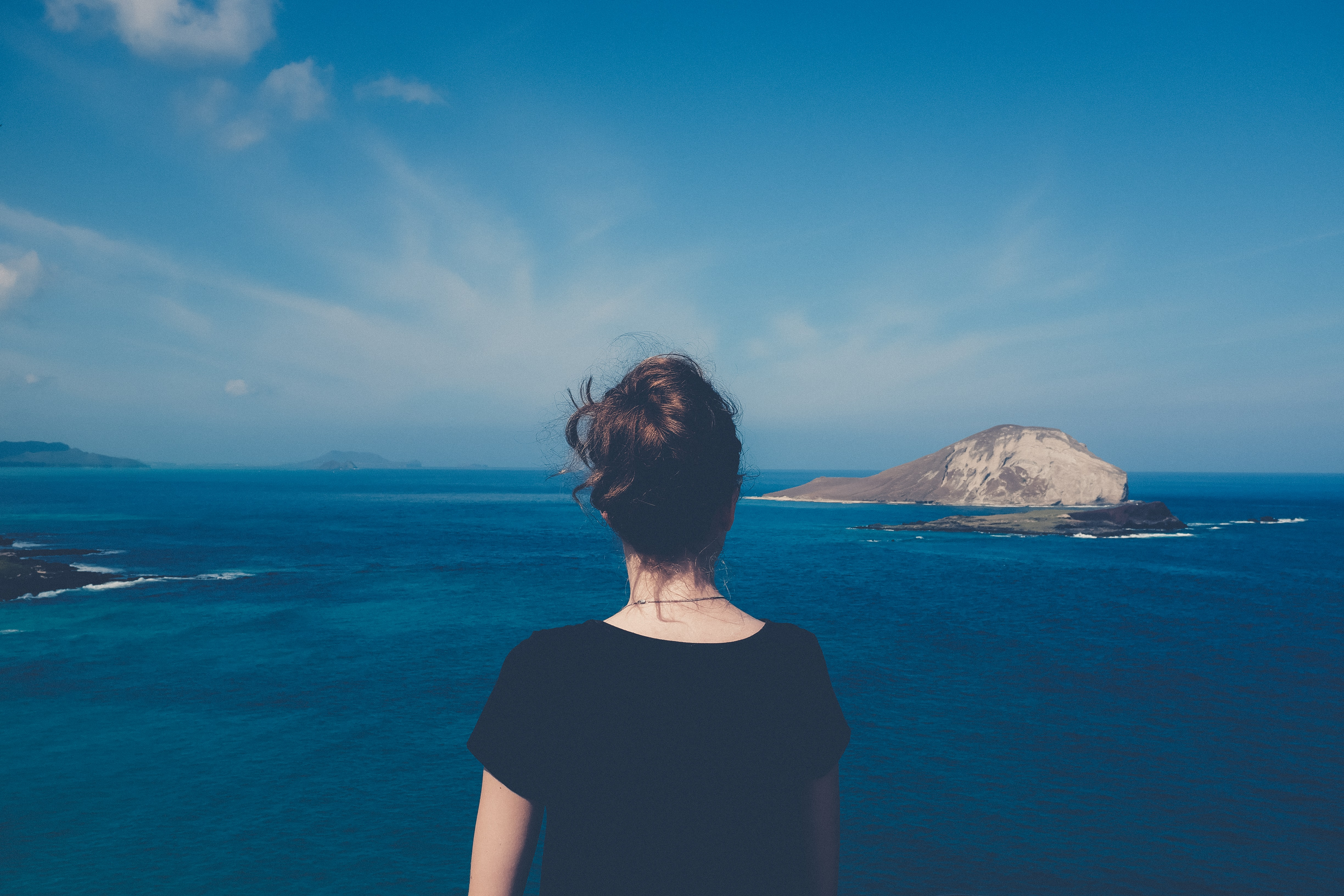 A woman standing in front of a sea of water with a rocky island in O'ahu