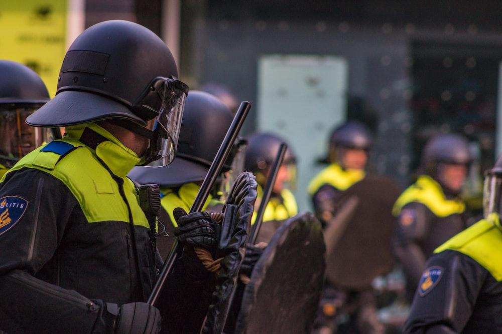 man in uniform holding baton and shield