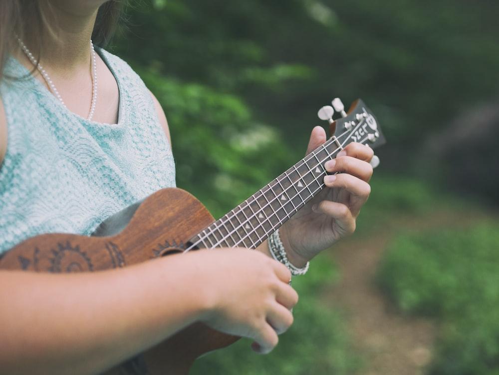 woman wearing blue sleeveless top holding brown tenor ukulele
